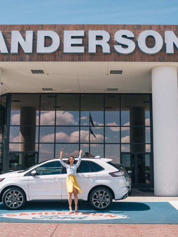 Ford Edge review with Sanderson Ford, lifestyle blogger Diana Elizabeth posing with a car