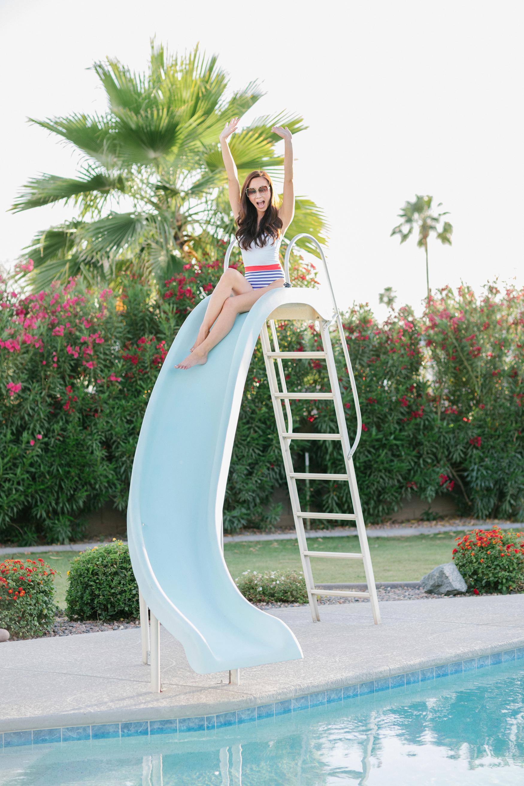 yandy affordable stylish swimsuits - on lifestyle blogger Diana Elizabeth - white sailor one piece swimsuit, posing on pool slide