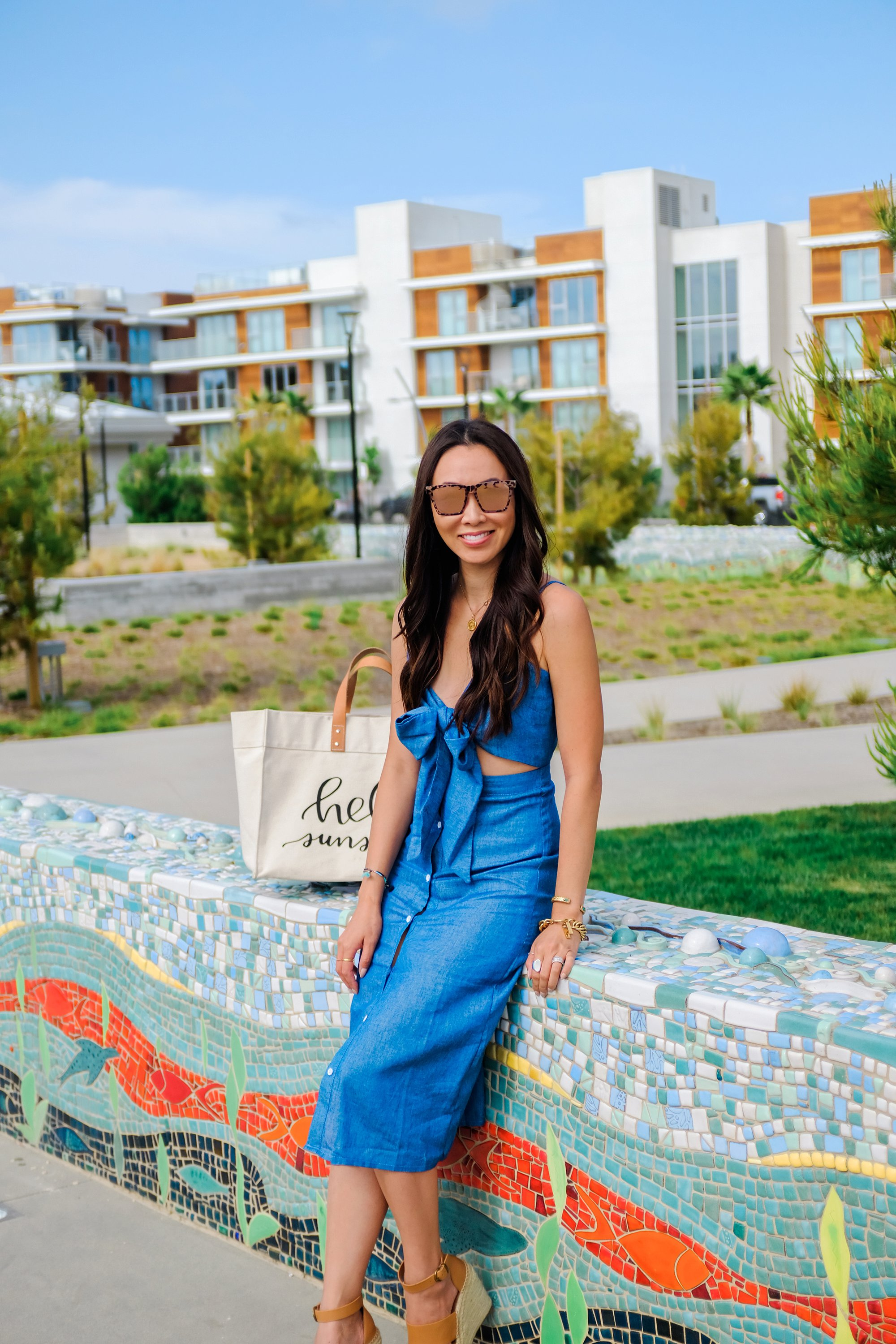 blue tie front button down midi dress misguided, lifestyle Phoenix blogger Diana Elizabeth walking at pacific City Huntington Beach carrying beach tote