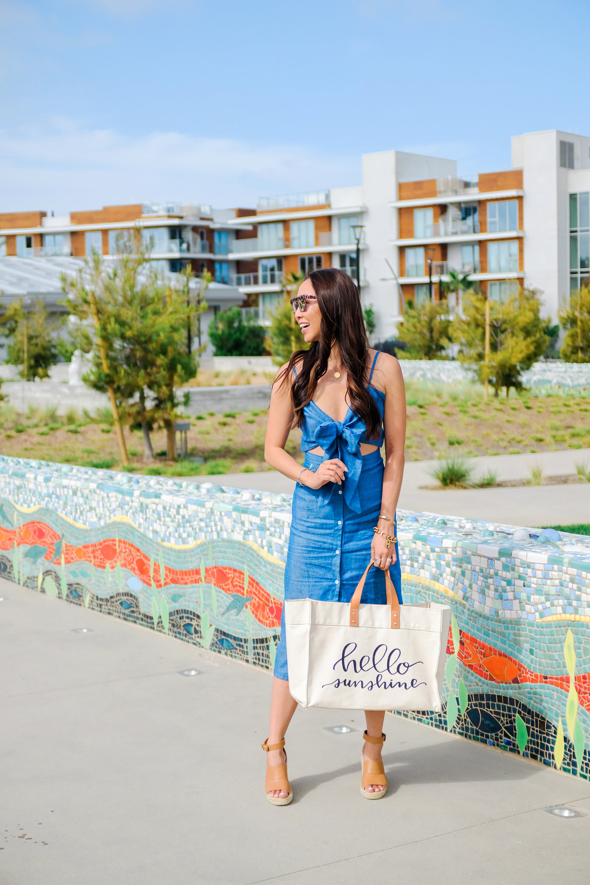 blue tie front button down midi dress misguided, lifestyle Phoenix blogger Diana Elizabeth walking at pacific City Huntington Beach carrying beach tote sitting on tile bench
