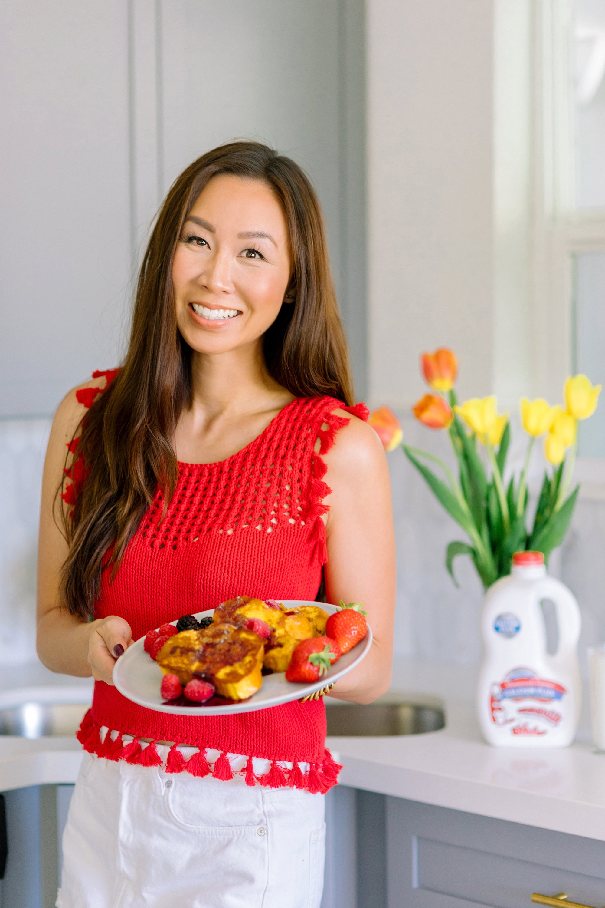 Lifestyle blogger in Phoenix Diana Elizabeth holding easy to make French toast recipe on the blog. Wearing red tassel crochet top. #frenchtoast #foodphotography