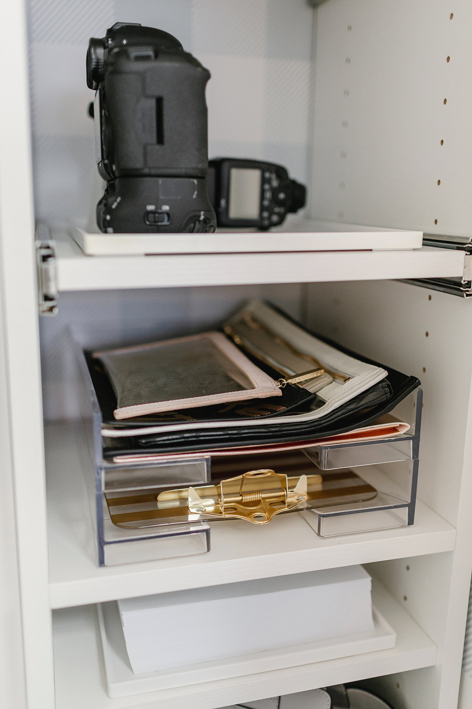 clear pouches for packing and travel: final reveal of office closet reveal belonging to photographer blogger Diana Elizabeth in phoenix arizona. created by California closets and with removable buffalo check wallpaper #office #closet #wallpaper #organization #lensorganization #lensdrawer