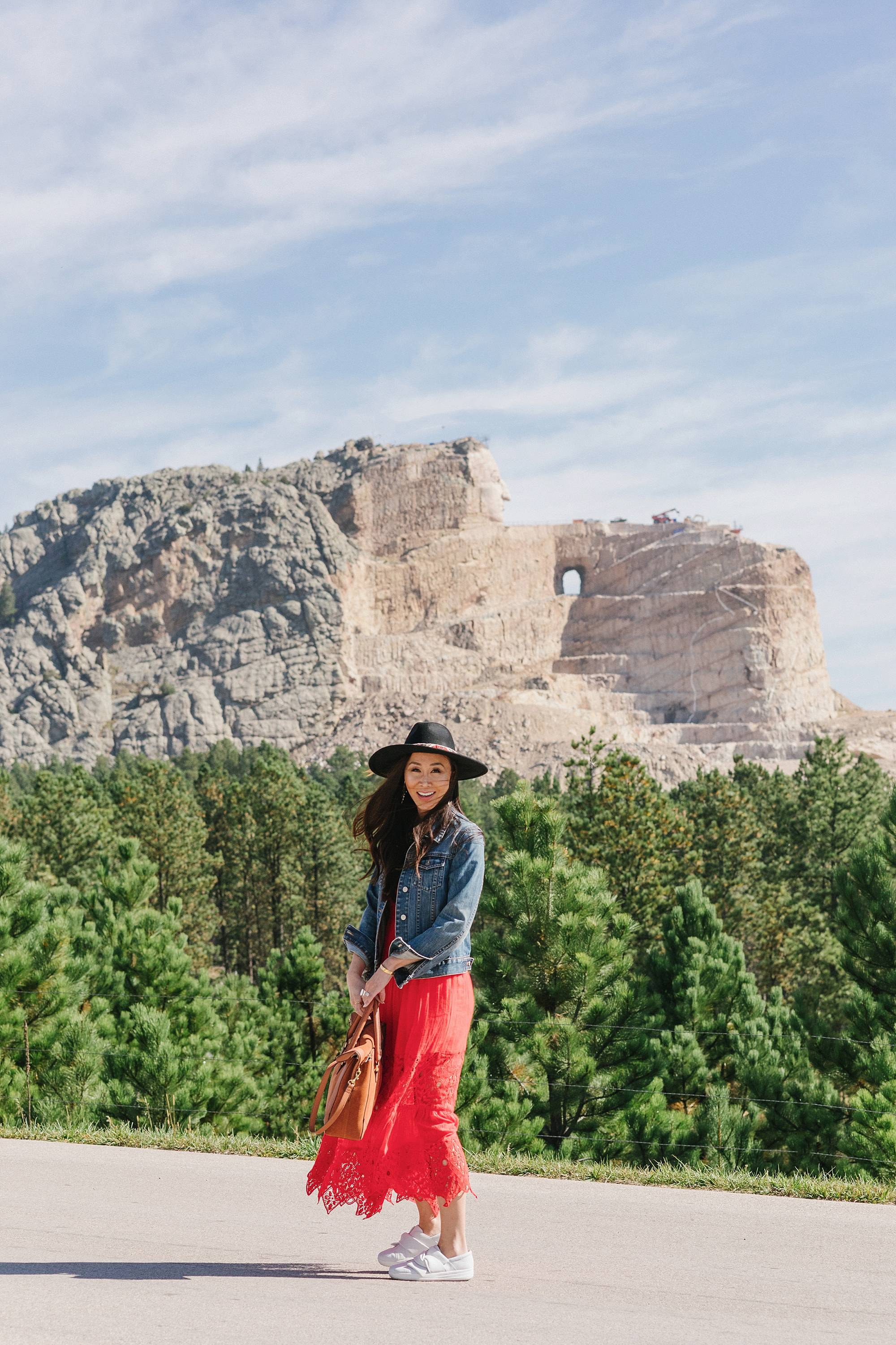 Crazy Horse Memorial in South Dakota - Diana Elizabeth Phoenix lifestyle blogger wearing red free people dress and wool hat and denim jacket posing with wind blowing