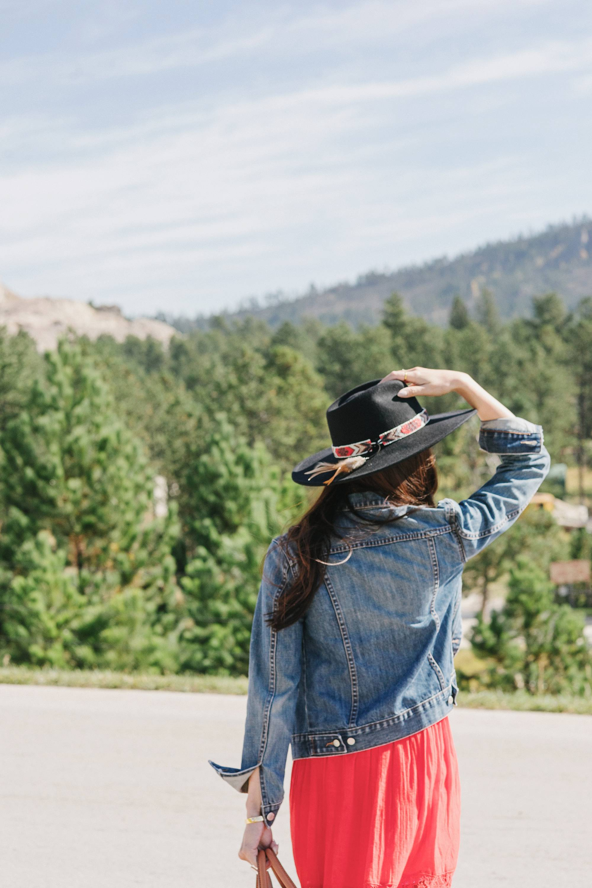 Crazy Horse Memorial in South Dakota - Diana Elizabeth Phoenix lifestyle blogger wearing red free people dress and wool hat and denim jacket posing and wearing white sneakers holding hat with beaded detail