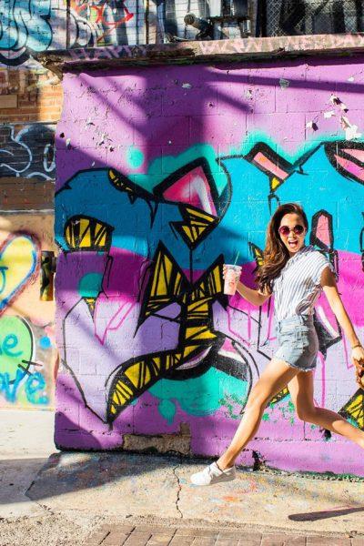 art alley graffiti walls in rapid city, South Dakota blogger Diana Elizabeth jumping in air