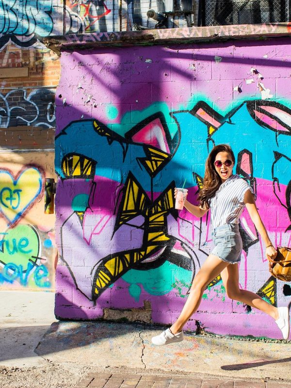 art alley graffiti walls in rapid city, South Dakota blogger Diana Elizabeth jumping in air