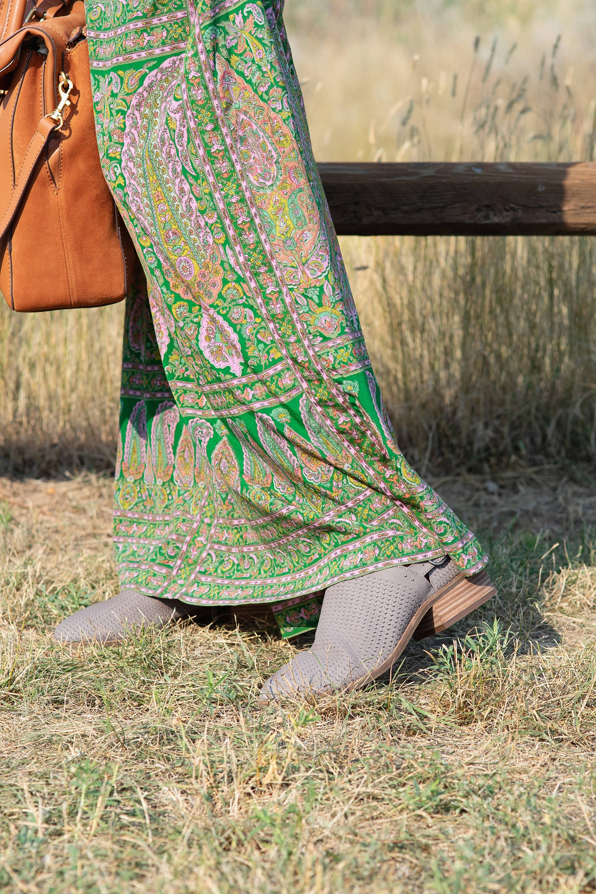 devil's tower in Wyoming, lifestyle blogger Diana Elizabeth in paisley skirt and open kit sweater and India hicks leather handbag