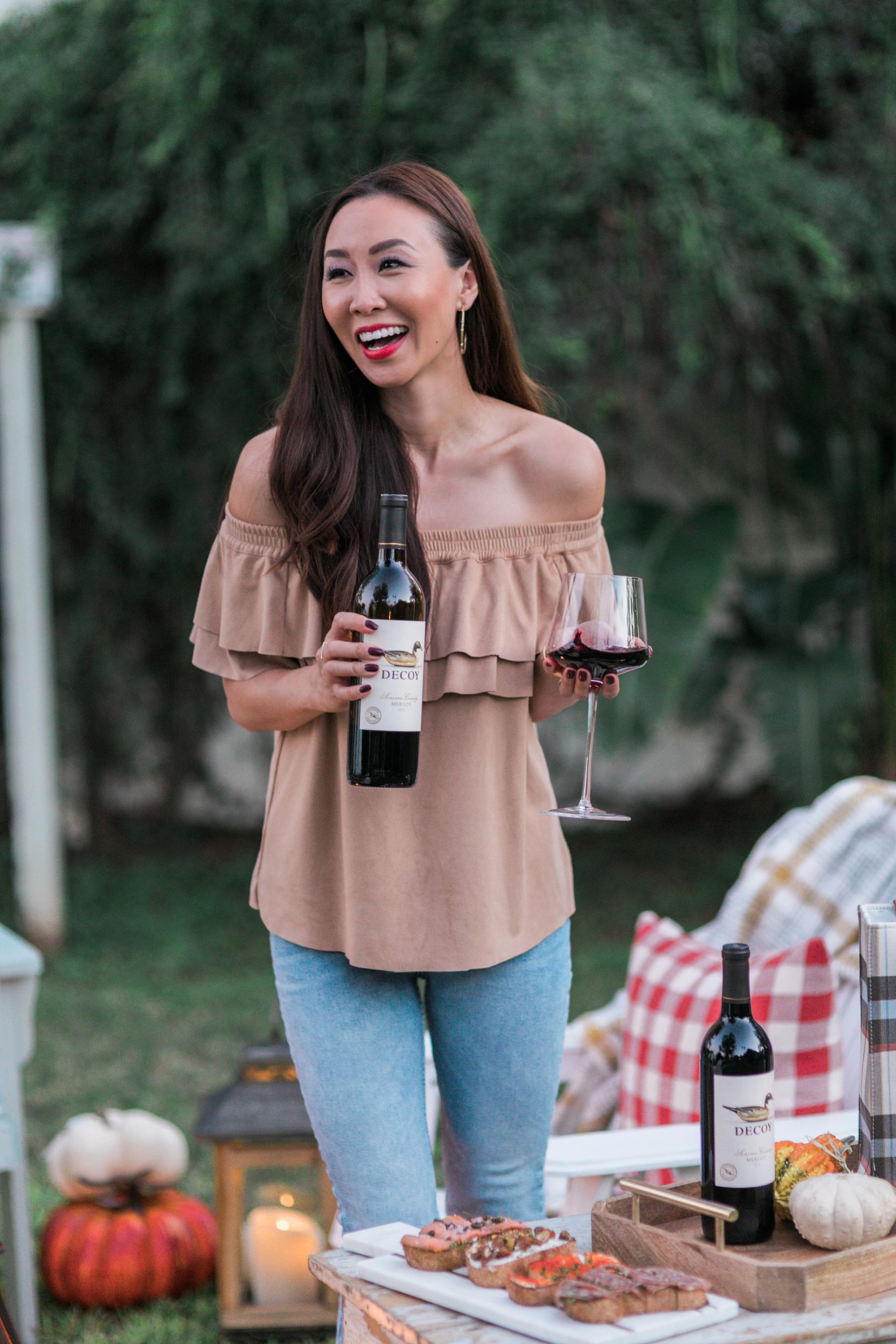 decoy wine merlot to celebrate merlot month of October! backyard setup with fire pit and bruschetta boards with blogger Diana Elizabeth - hay bales pumpkins, gourds and cozy blankets and pillows