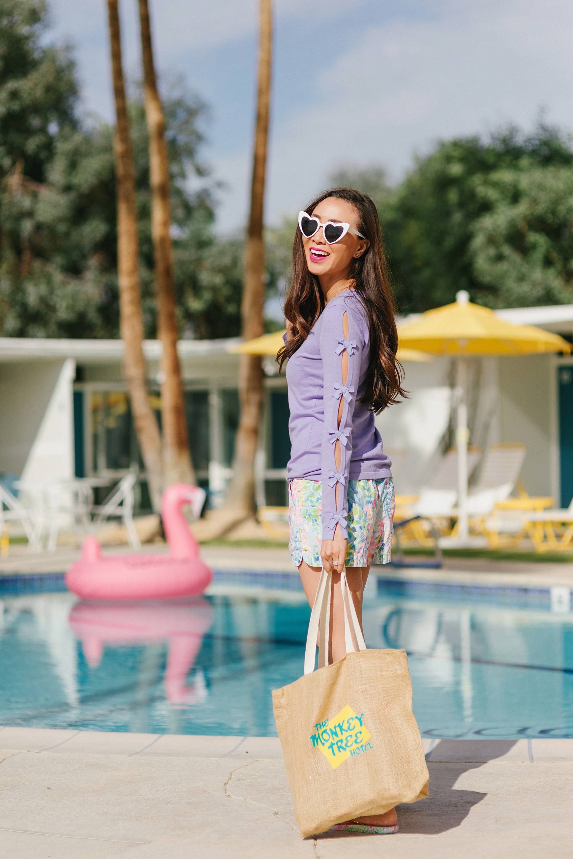 the monkey tree inn Palm Springs wearing Lilly pulitzer on phoenix travel lifestyle blogger Diana Elizabeth holding a tote by the pool and white heart sunnies