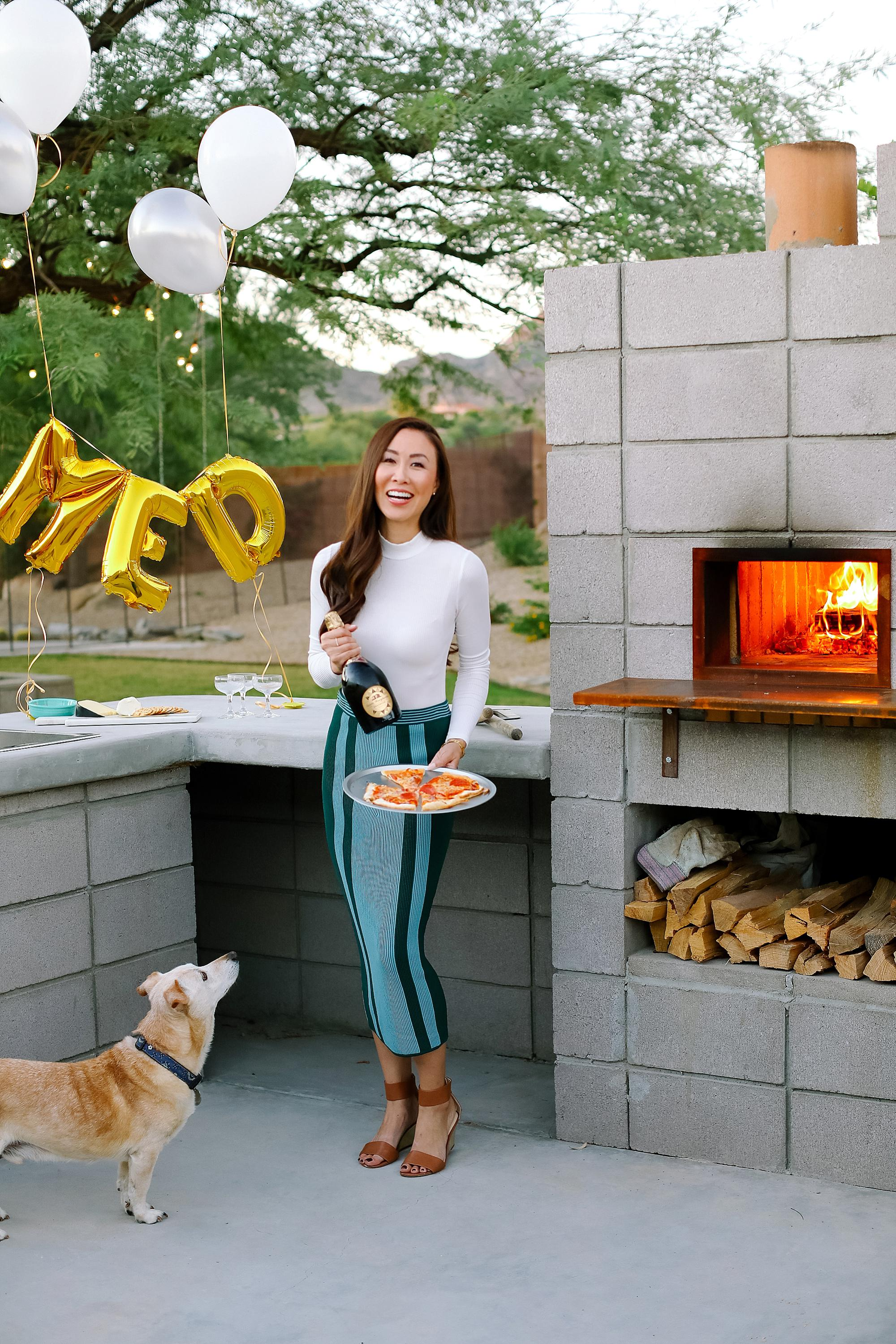 santa margherita prosecco superiore set by mylar alphabet balloons and the an outdoor pizza fireplace lifestyle blogger Diana Elizabeth in phoenix arizona holding pizza