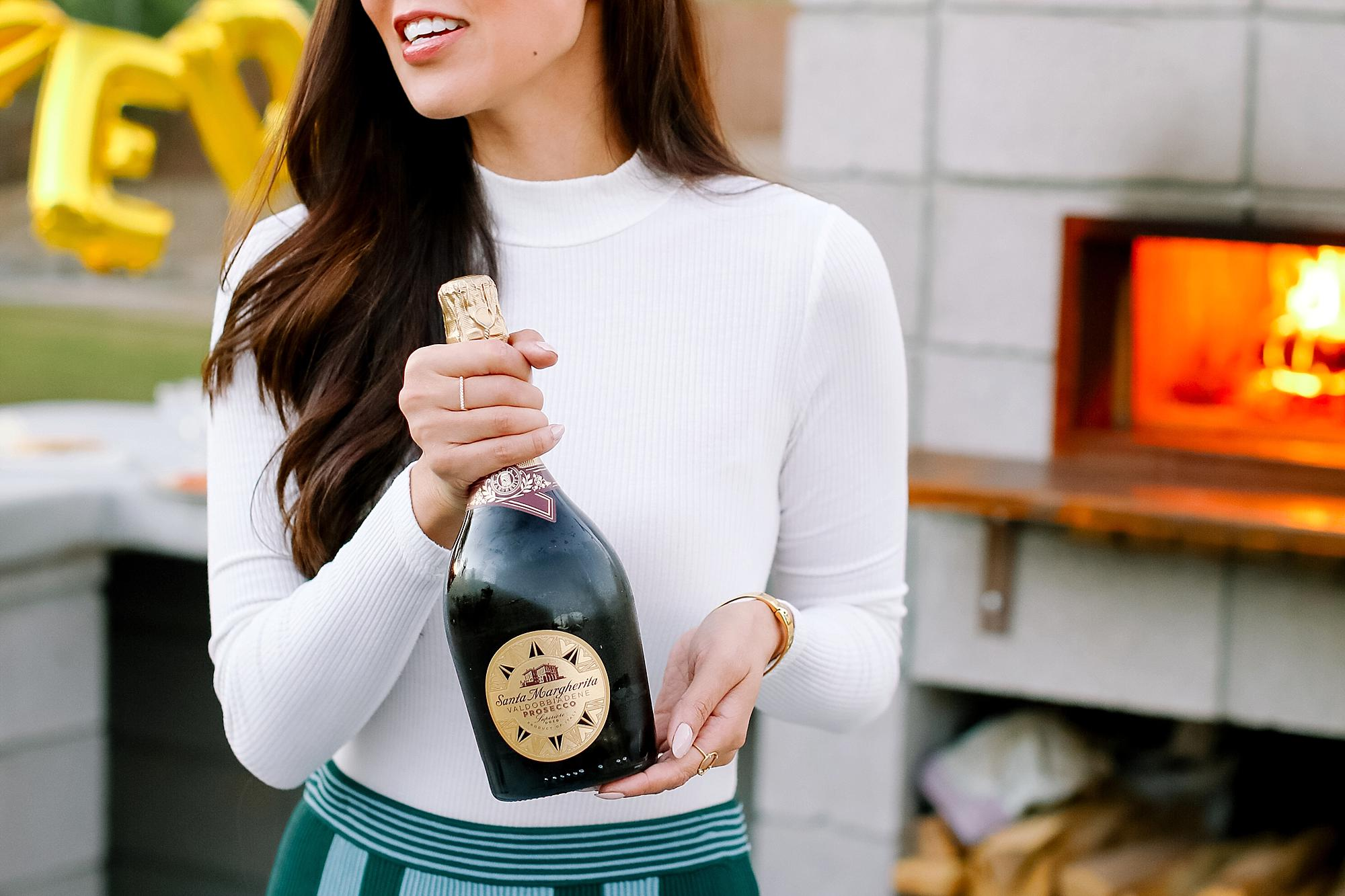 santa margherita prosecco superiore set by mylar alphabet balloons and the an outdoor pizza fireplace lifestyle blogger Diana Elizabeth in phoenix arizona holding Santa margherita