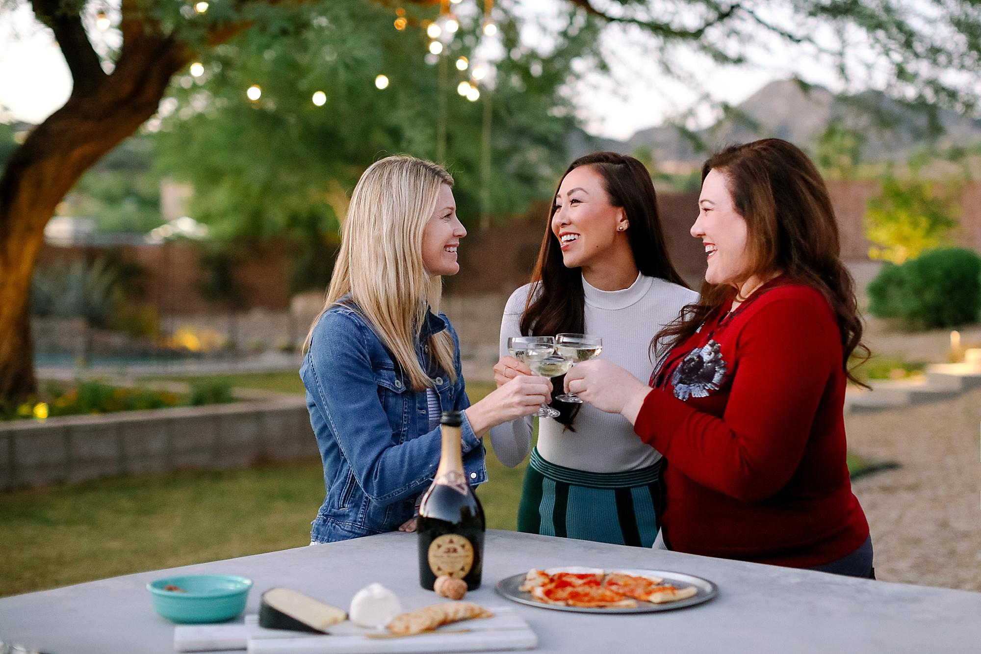 santa margherita prosecco superiore set by mylar alphabet balloons and the an outdoor pizza fireplace lifestyle blogger Diana Elizabeth in phoenix arizona toasting with friends