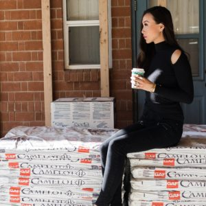 GAF roofing Camelot II designer shingles in Barkwood on lifestyle home blogger Diana Elizabeth sitting on the special delivery of roof shingles!