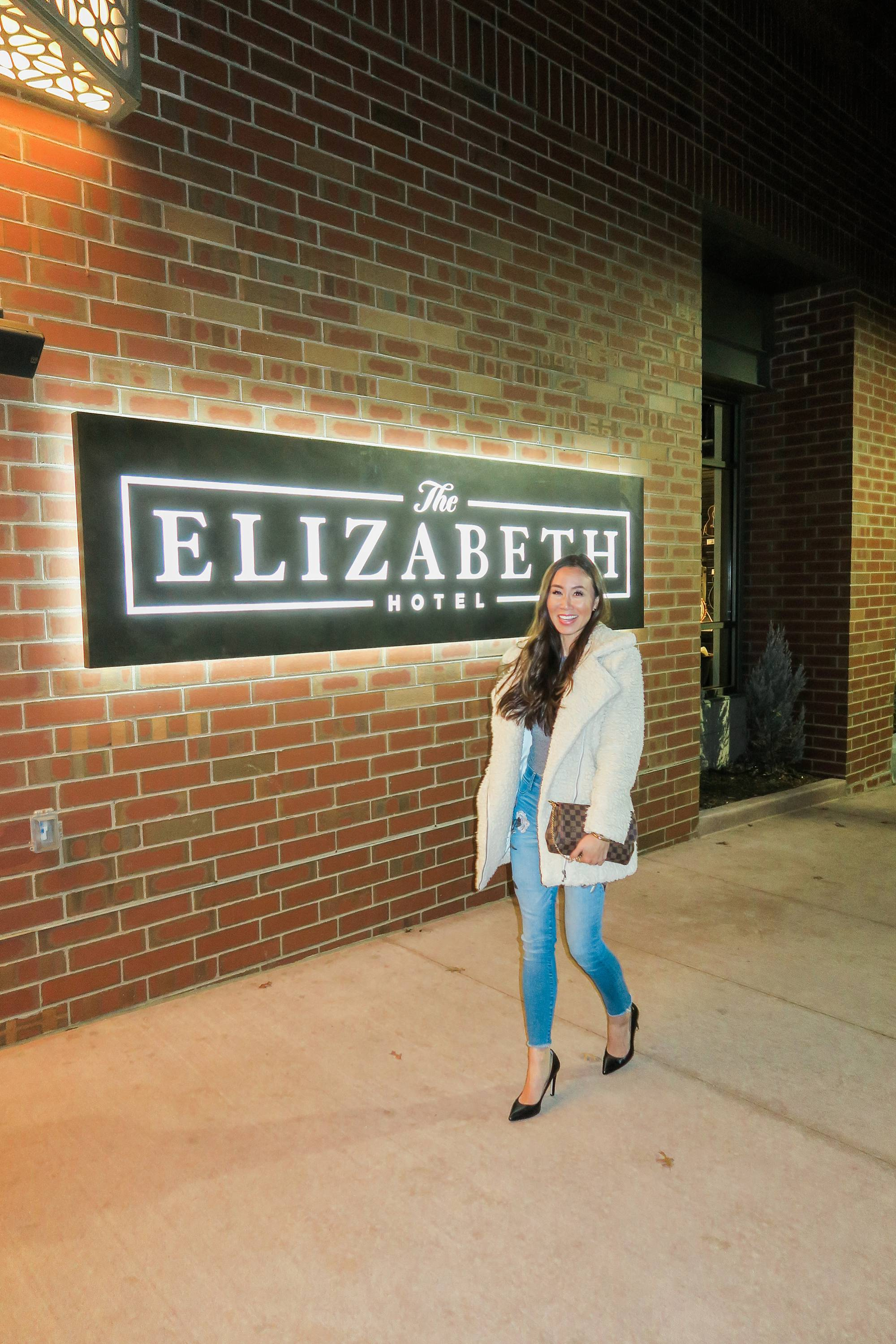 the Elizabeth hotel in Fort Collins, Colorado, lifestyle blogger Diana Elizabeth walking in front of the hotel sign