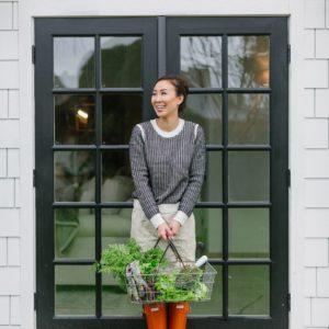 garden blog into the garden wet winter day with lifestyle blogger Diana Elizabeth holding garden veggie basket #garden #raisedgarenbeds #gardener