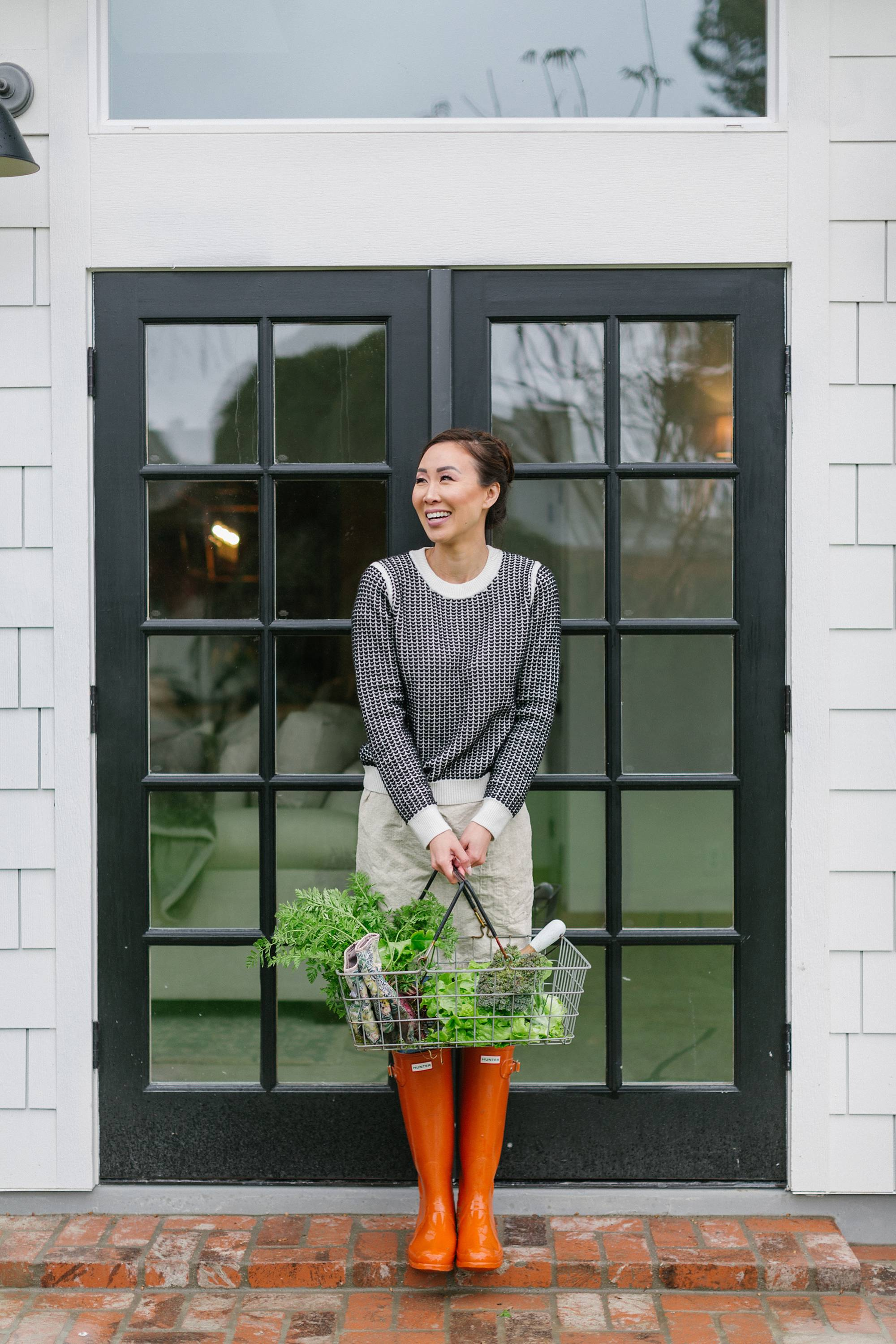garden blog into the garden wet winter day with lifestyle blogger Diana Elizabeth holding garden veggie basket #garden #raisedgarenbeds #gardener