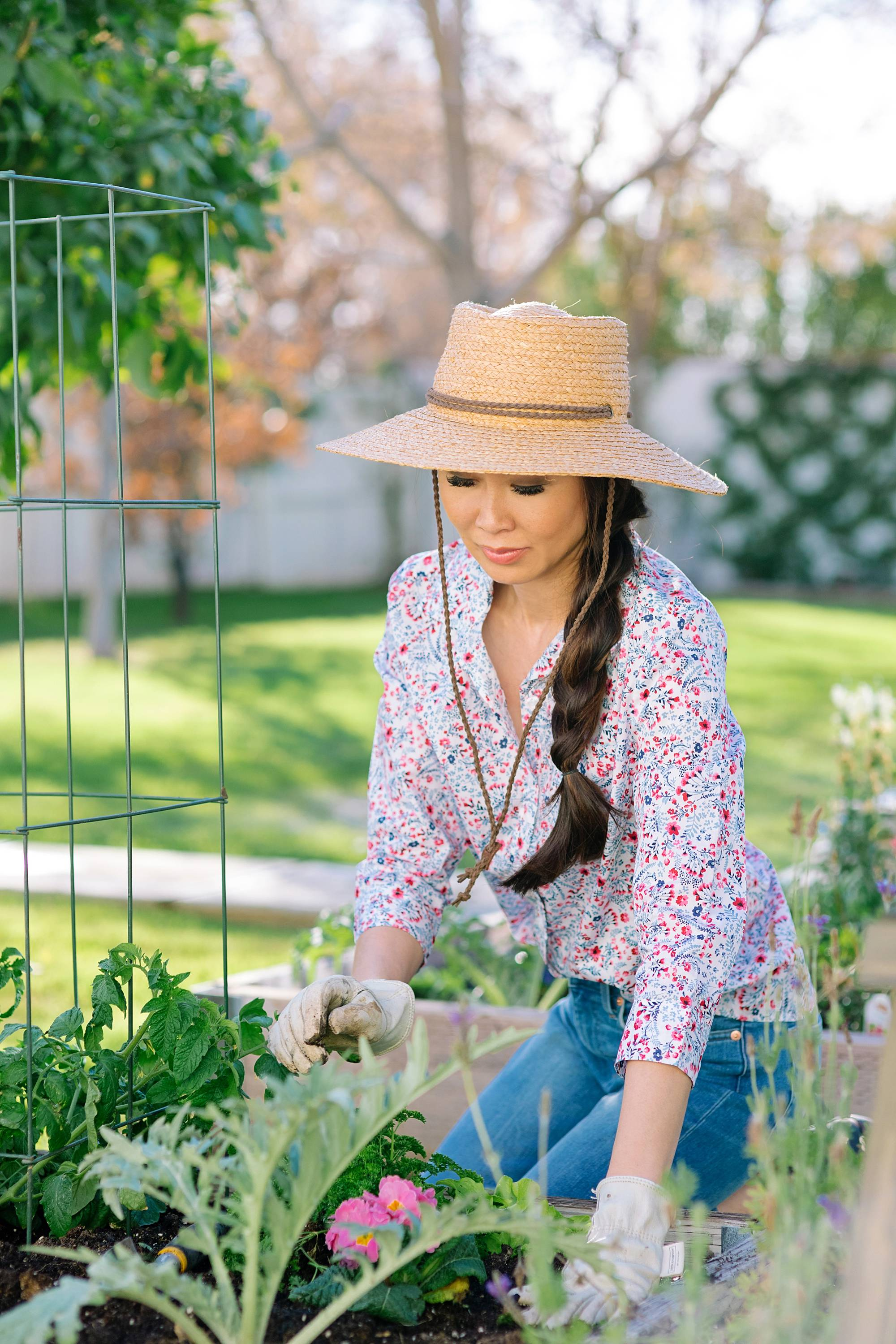 garden lifestyle blogger Diana Elizabeth in backyard garden raised garden beds in phoenix arizona wearing floral print shirt