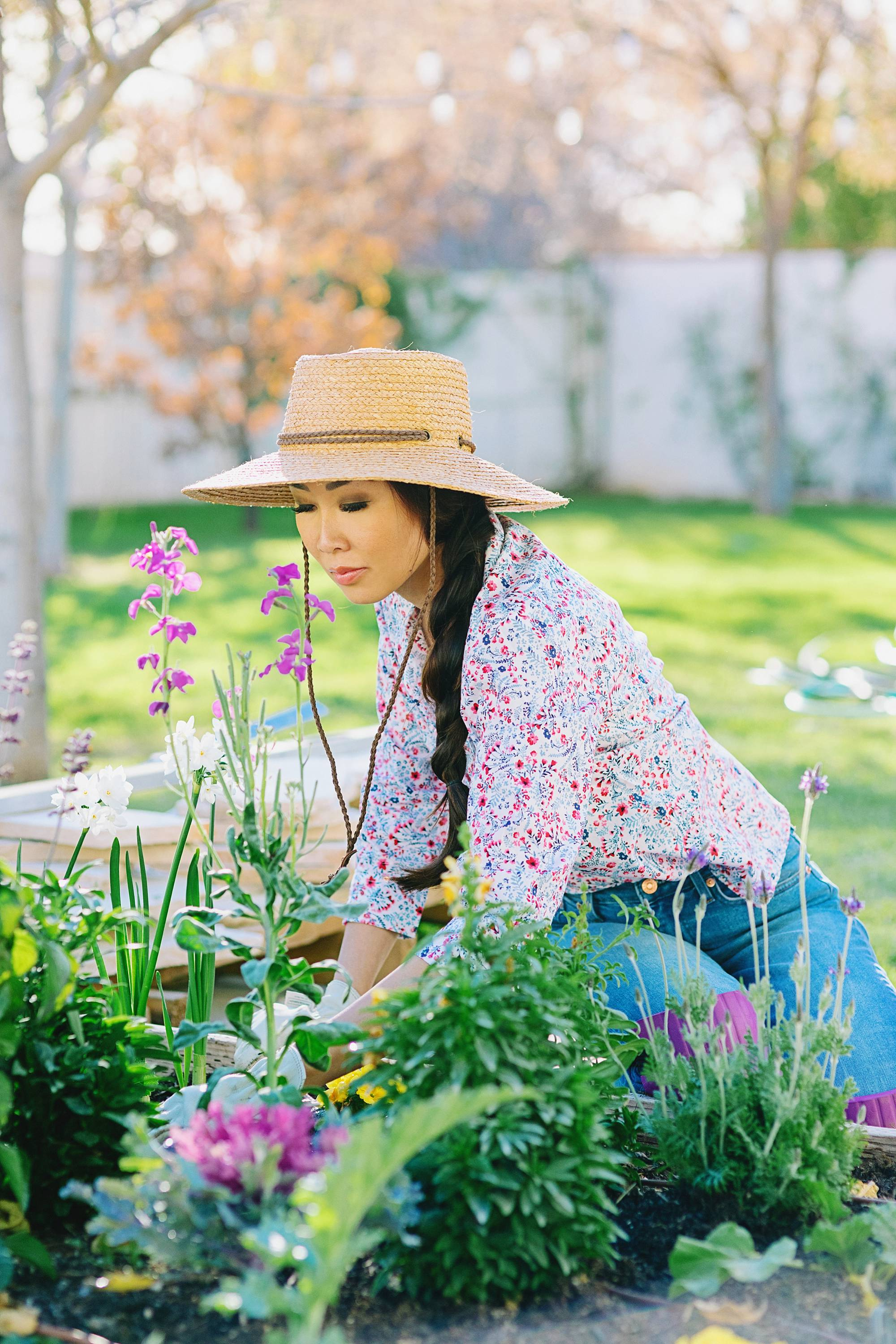 Diana Elizabeth in her backyard garden in Phoenix arizona wearing a floral print shirt, raised garden beds