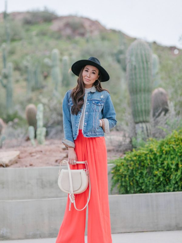 denim jacket orange pants black hat in desert landscape at desert botanical gardens