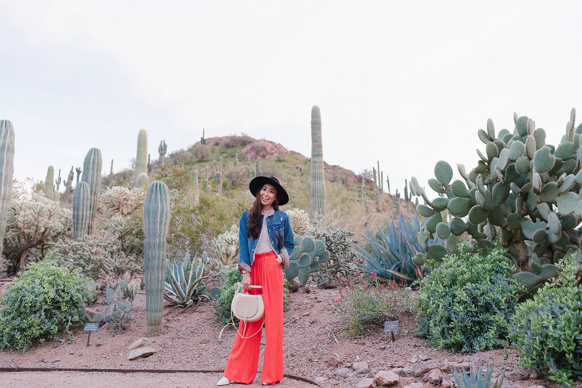 denim jacket orange pants black hat in desert landscape at desert botanical gardens