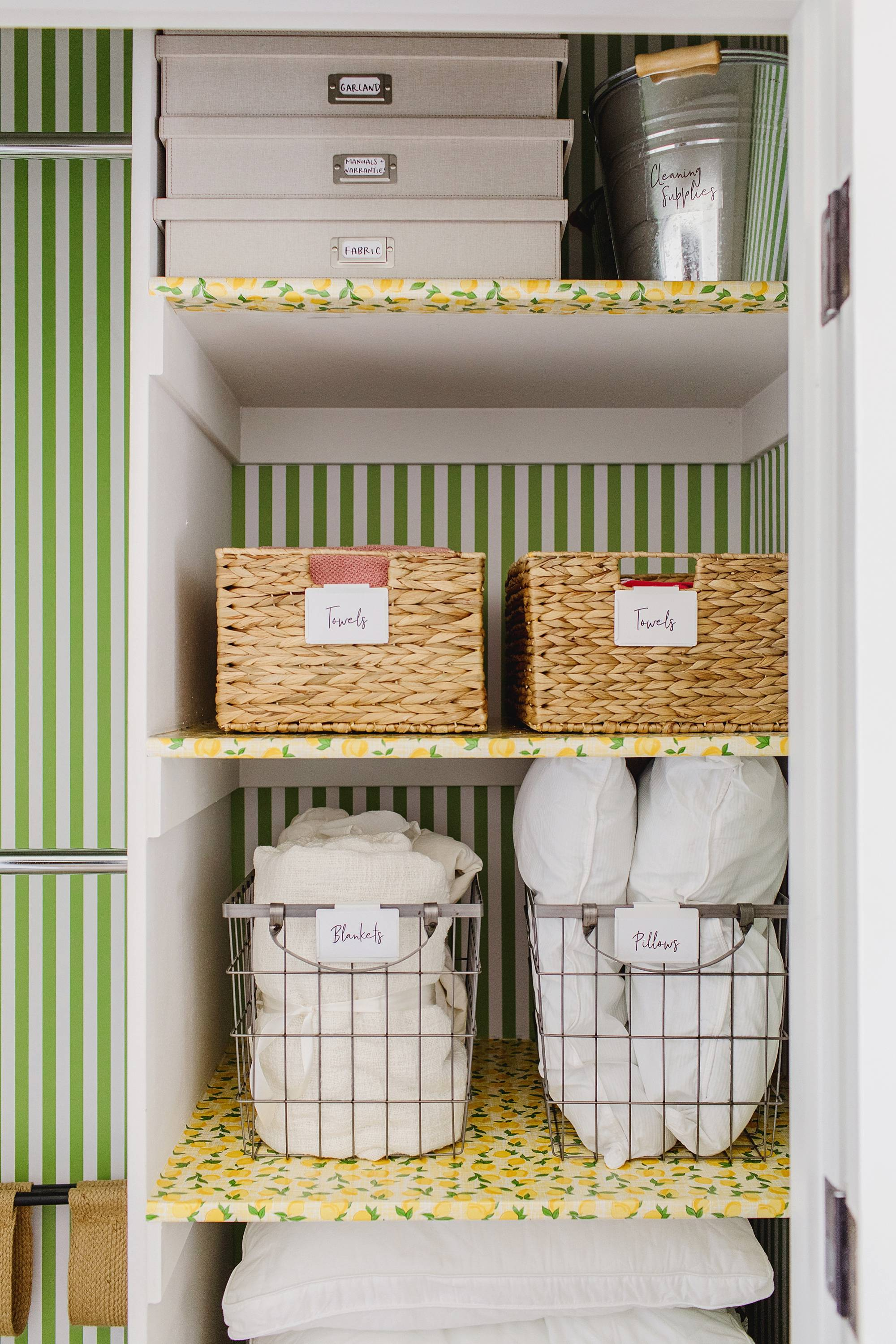 closet with wallpaper for guests - green white stripe and lemon shelf liner