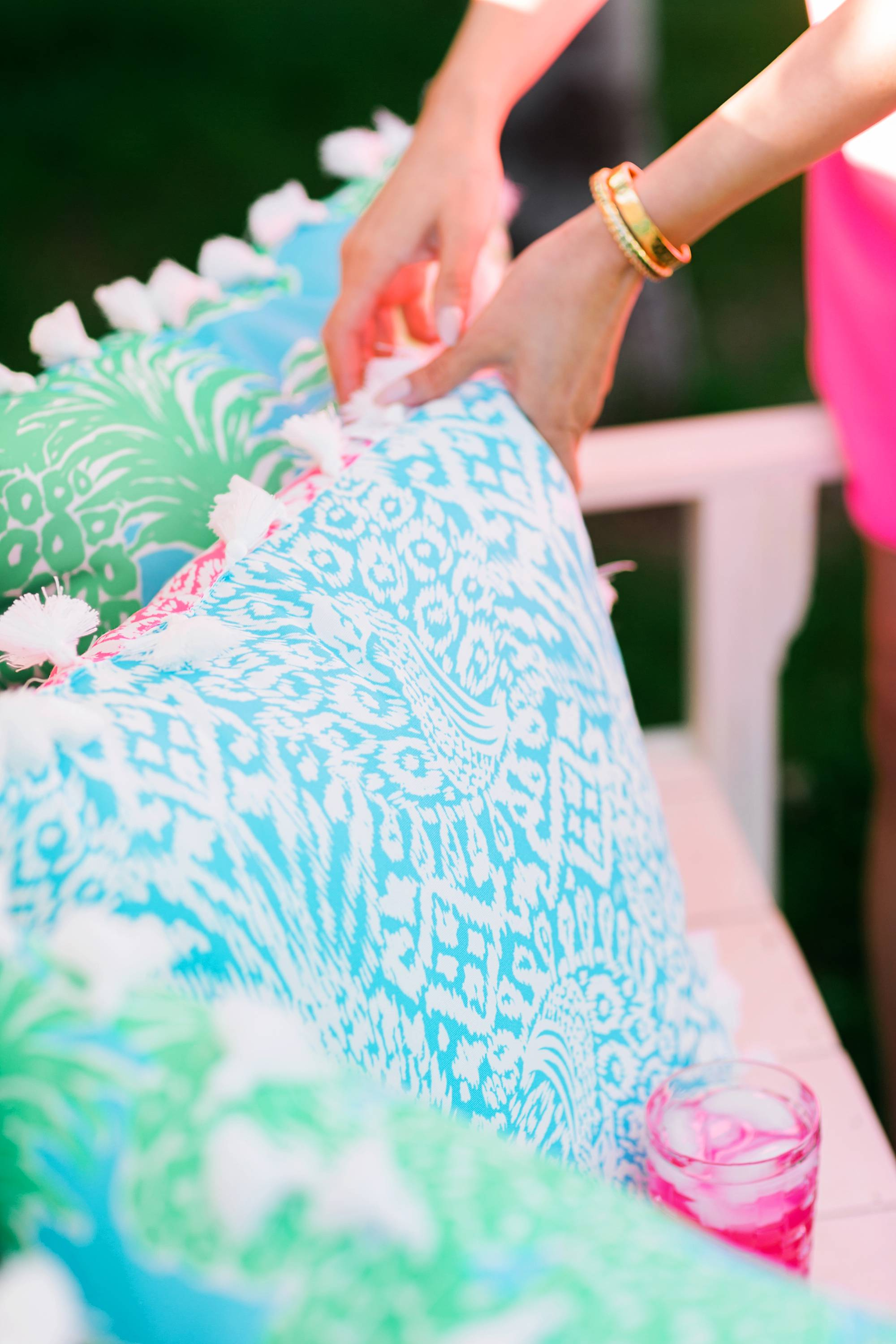 Lilly Pulitzer x Pottery Barn collaboration Spring summer 2019 on white bench with lilly Pulitzer outdoor pillows