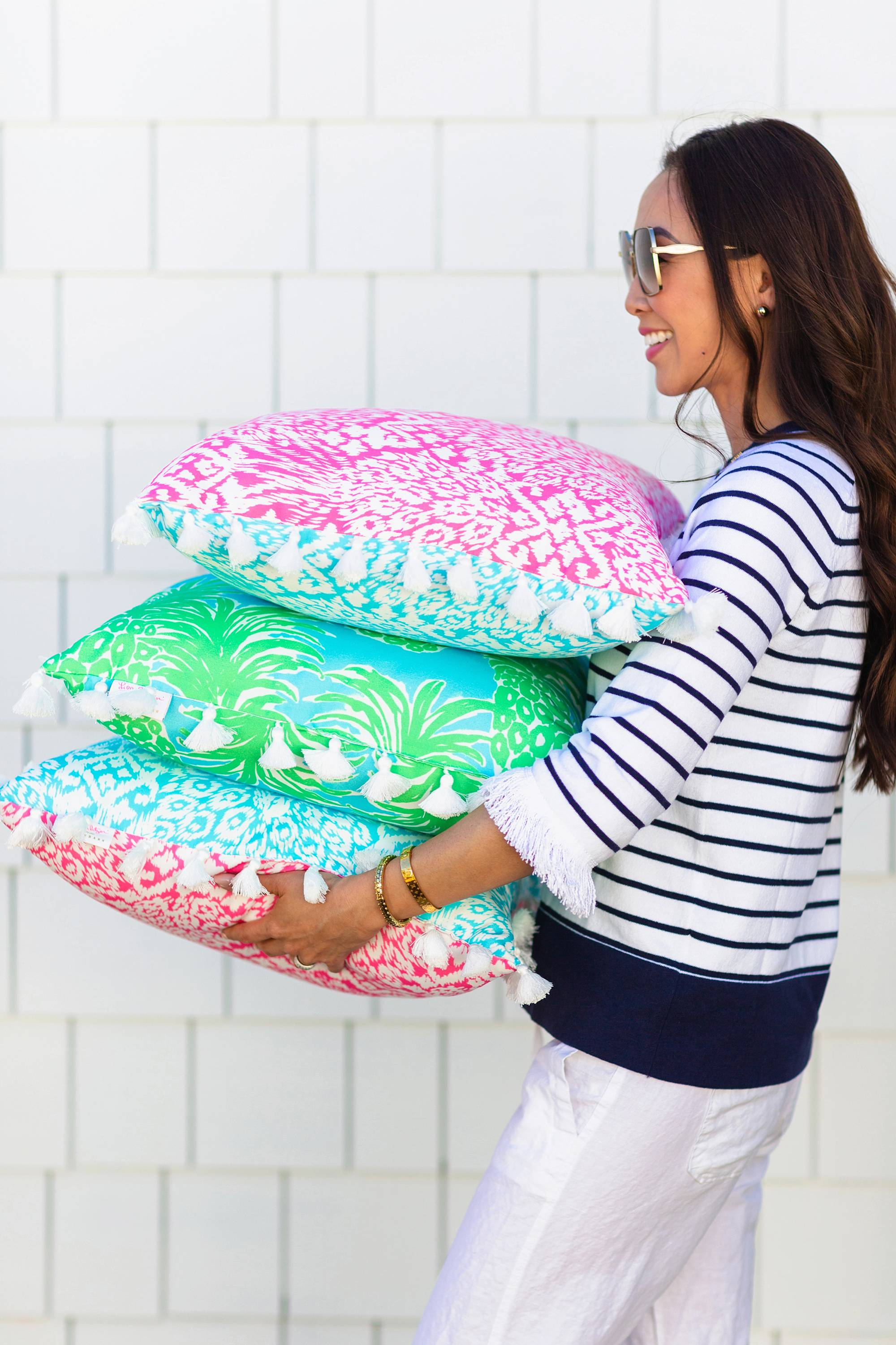 Lilly Pulitzer x Pottery Barn collaboration Spring summer 2019 carrying pile of lilly Pulitzer outdoor pillows
