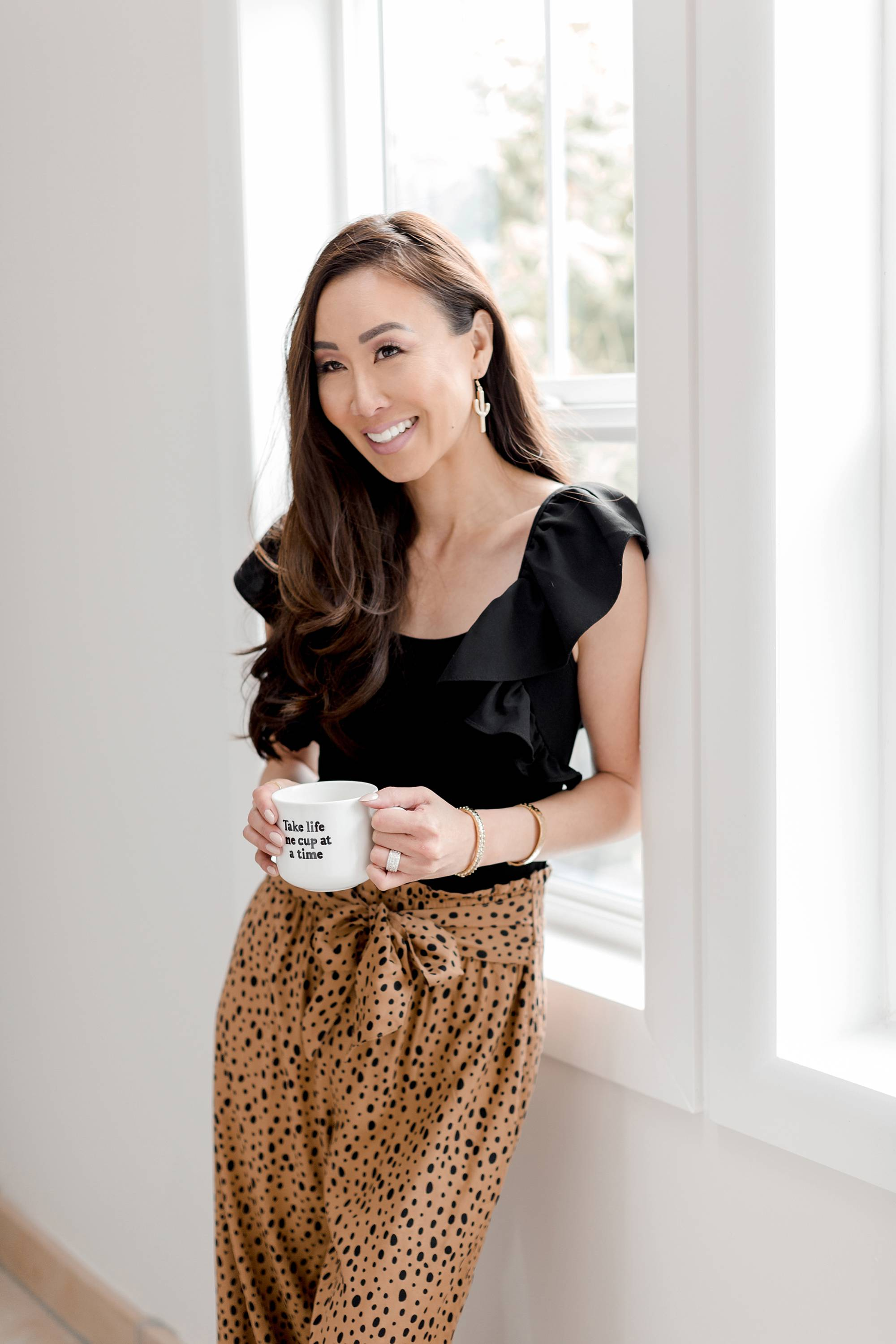 take life one cup at a time mug, leopard print pants from Anthropologie and ruffle top, cactus earrings on lifestyle blogger Diana Elizabeth against the window