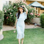 blue lace dress with garden hat from terrain nestled between pink roses against the wall - lifestyle blogger Diana Elizabeth phoenix scottsdale arizona holding rose