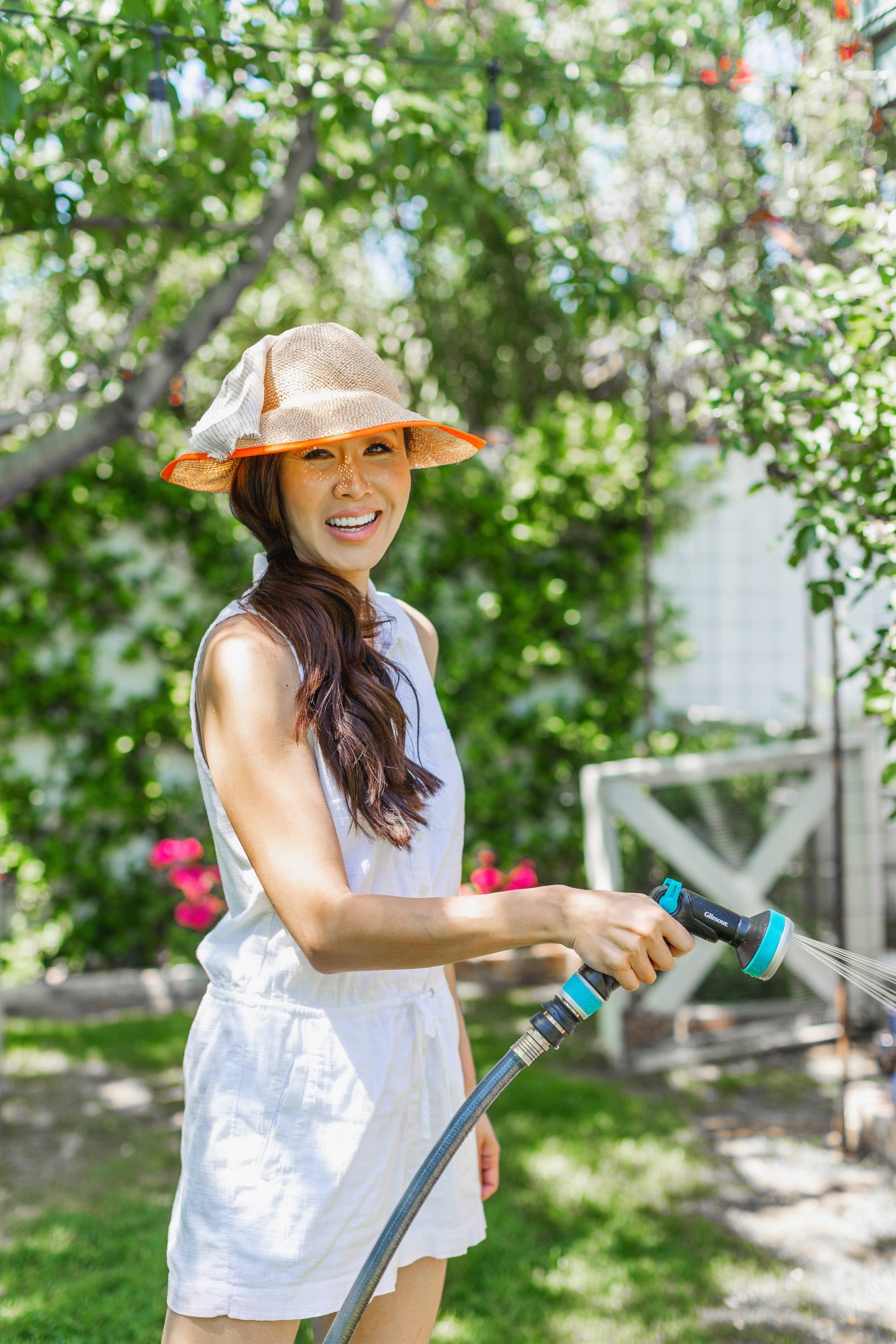 gardening with hat on with Gilmour hose
