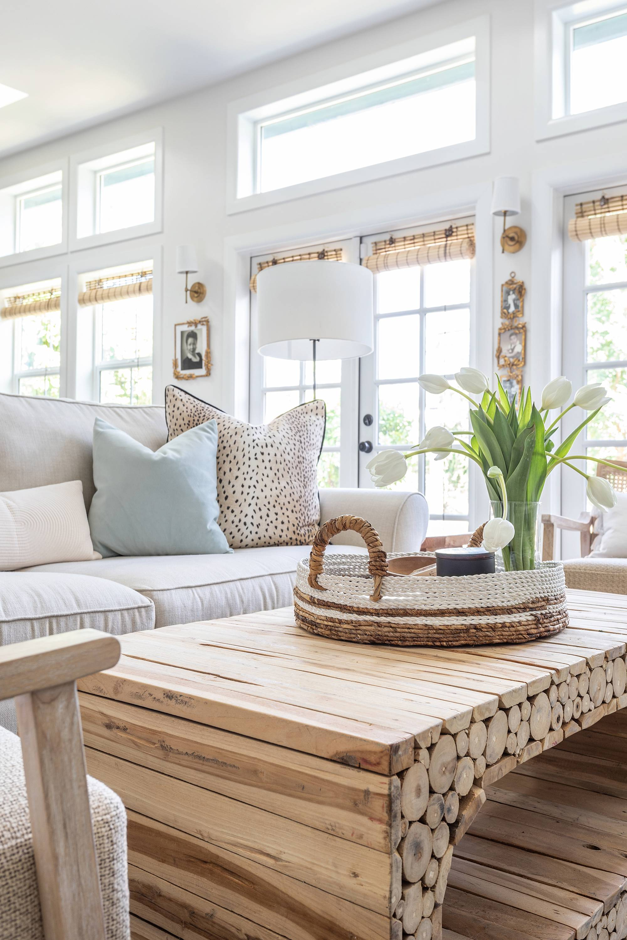 drift wood coastal coffee wood table bamboo shades in white room living family room