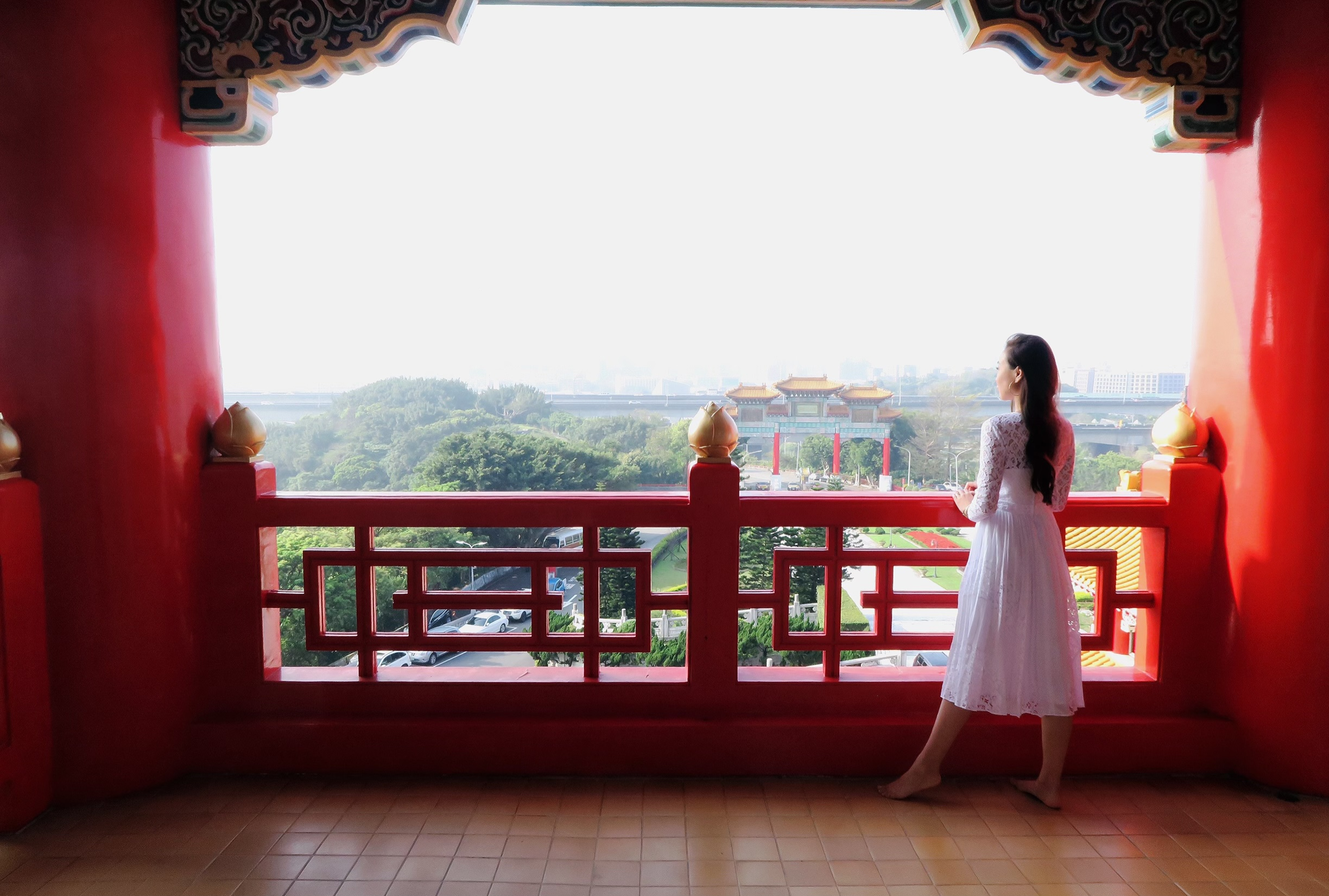Grand hotel balcony in Taipei Taiwan Diana Elizabeth Phoenix travel blogger wearing white dress looking into city