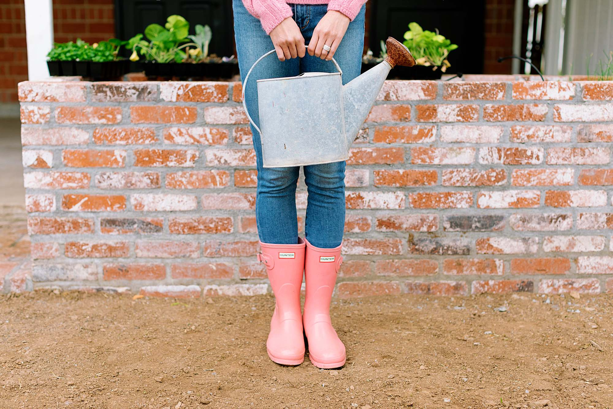 pink hunter boots in front of garden beds holding vintage garden watering can #hunterboots #garden