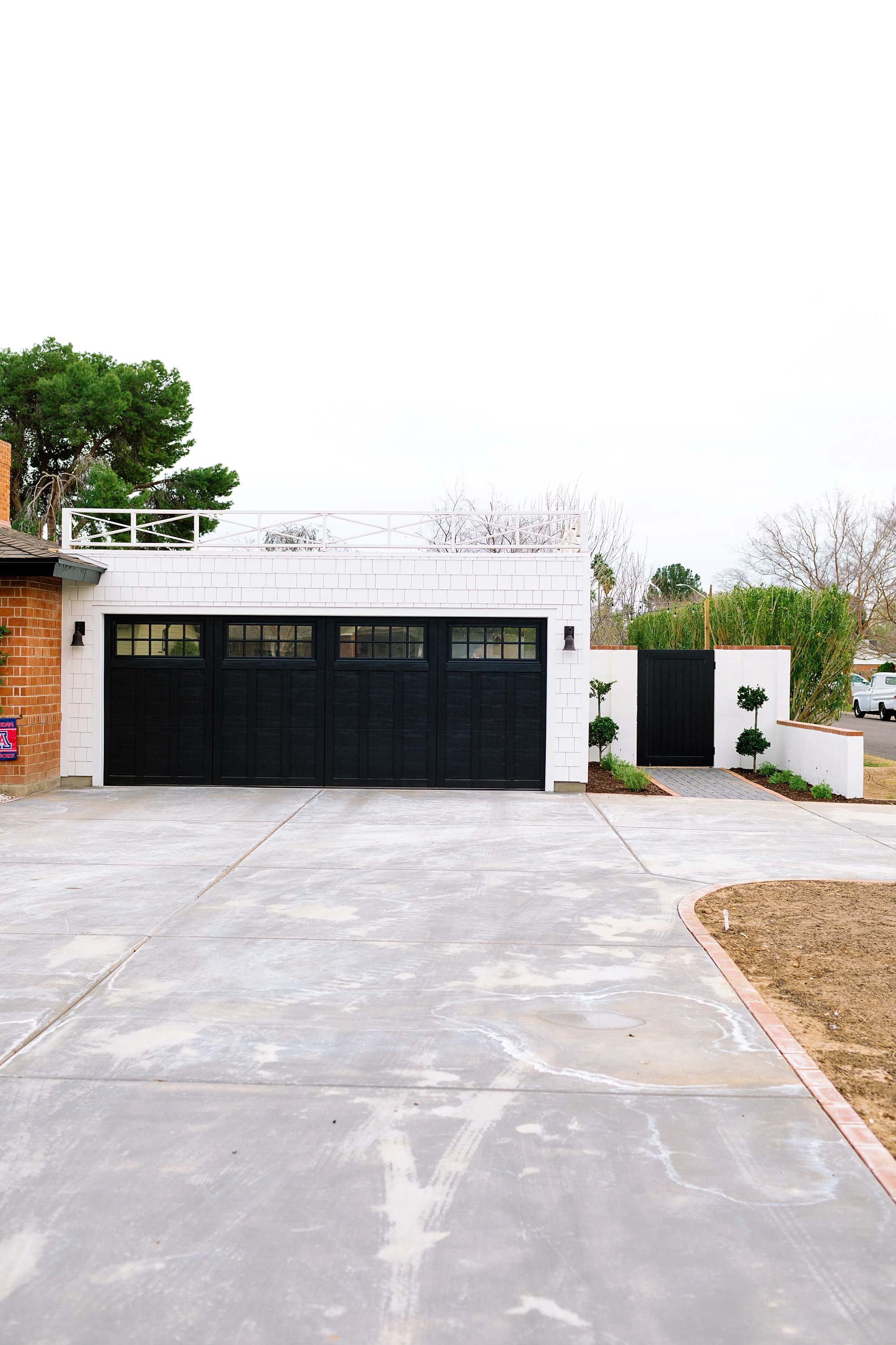 flat roof white black red brick house side gate of garage to garden area double topiaries and fern leaf lavender