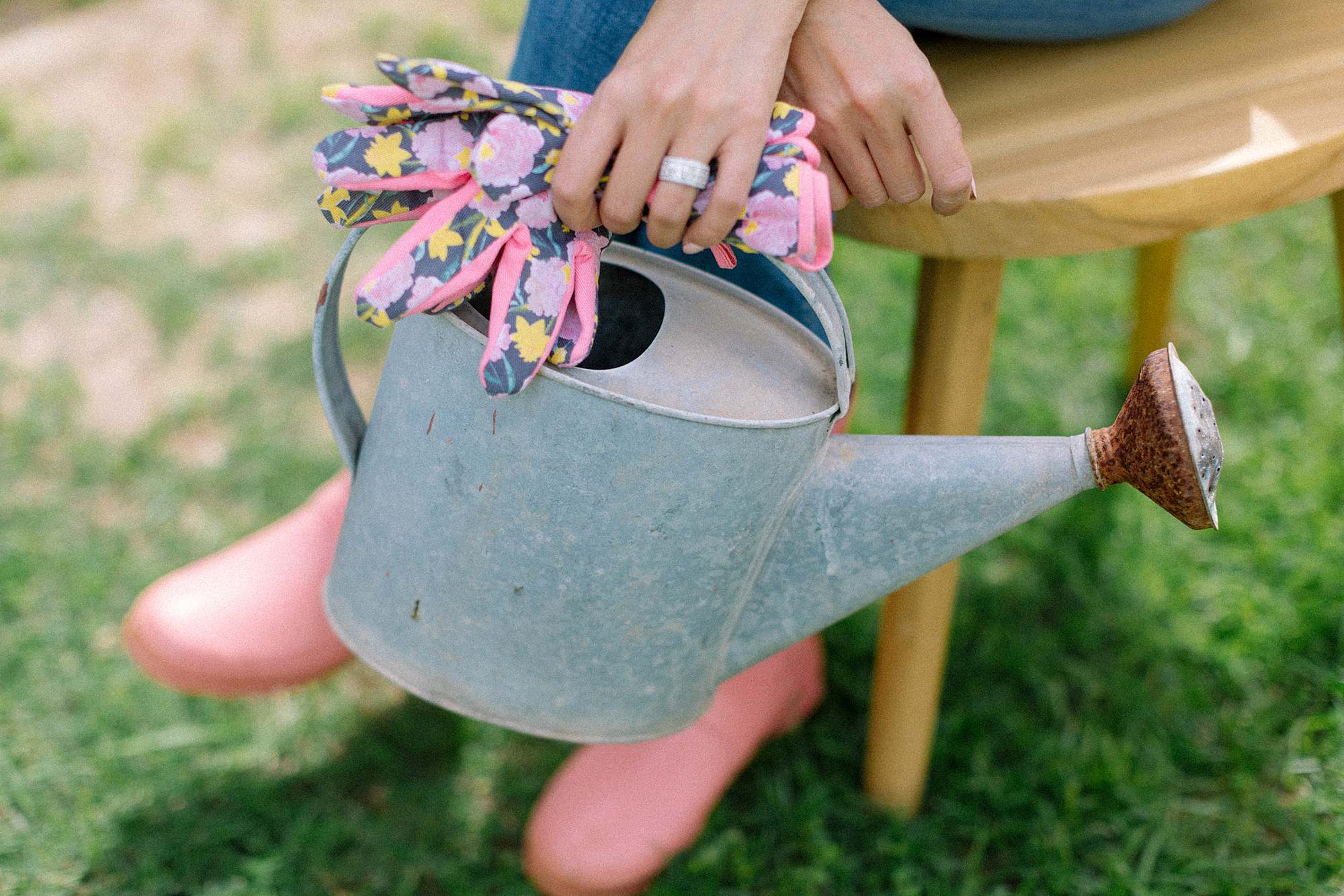 holding watering can and garden gloves floral