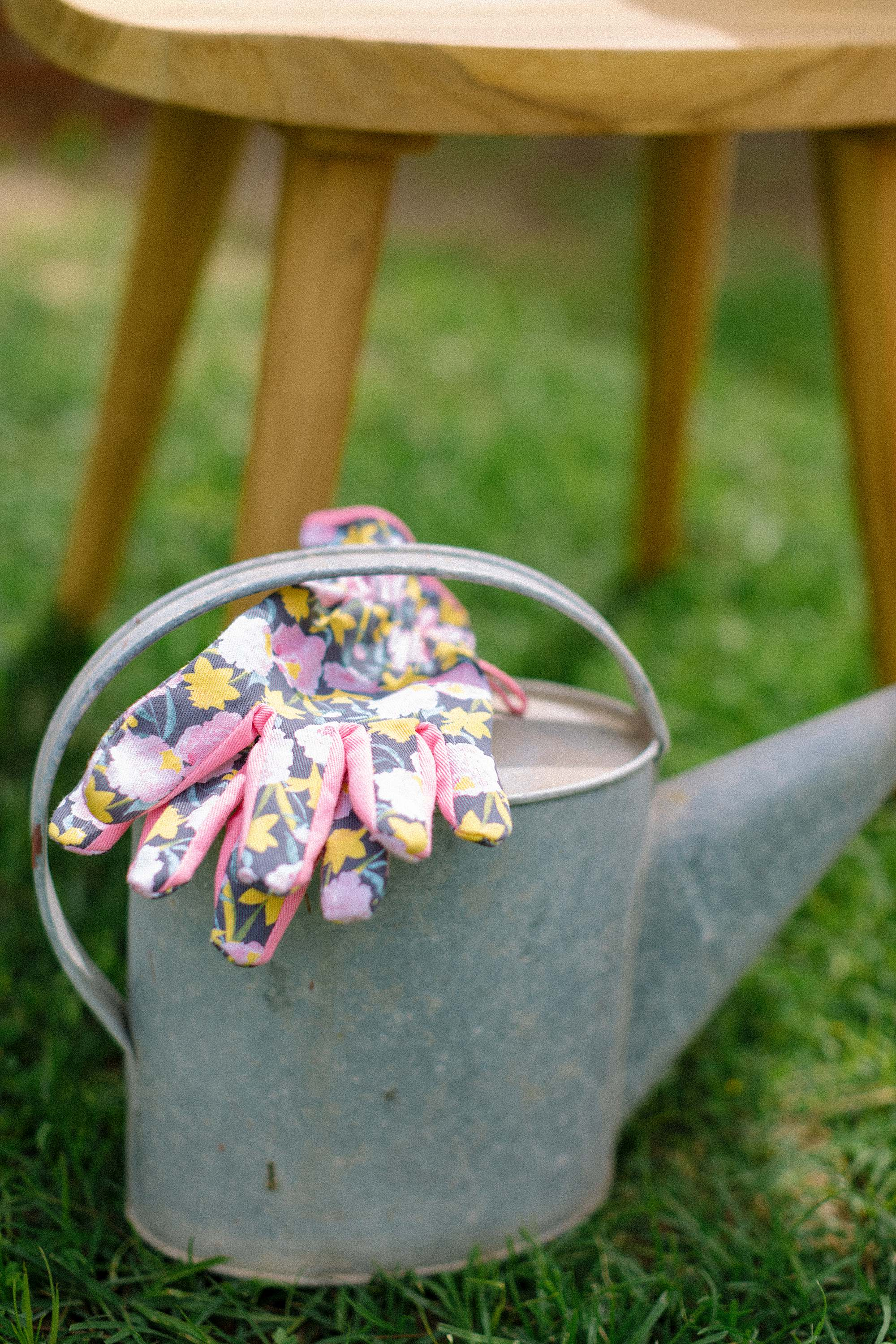 floral garden gloves on antique watering can gardening shot photography