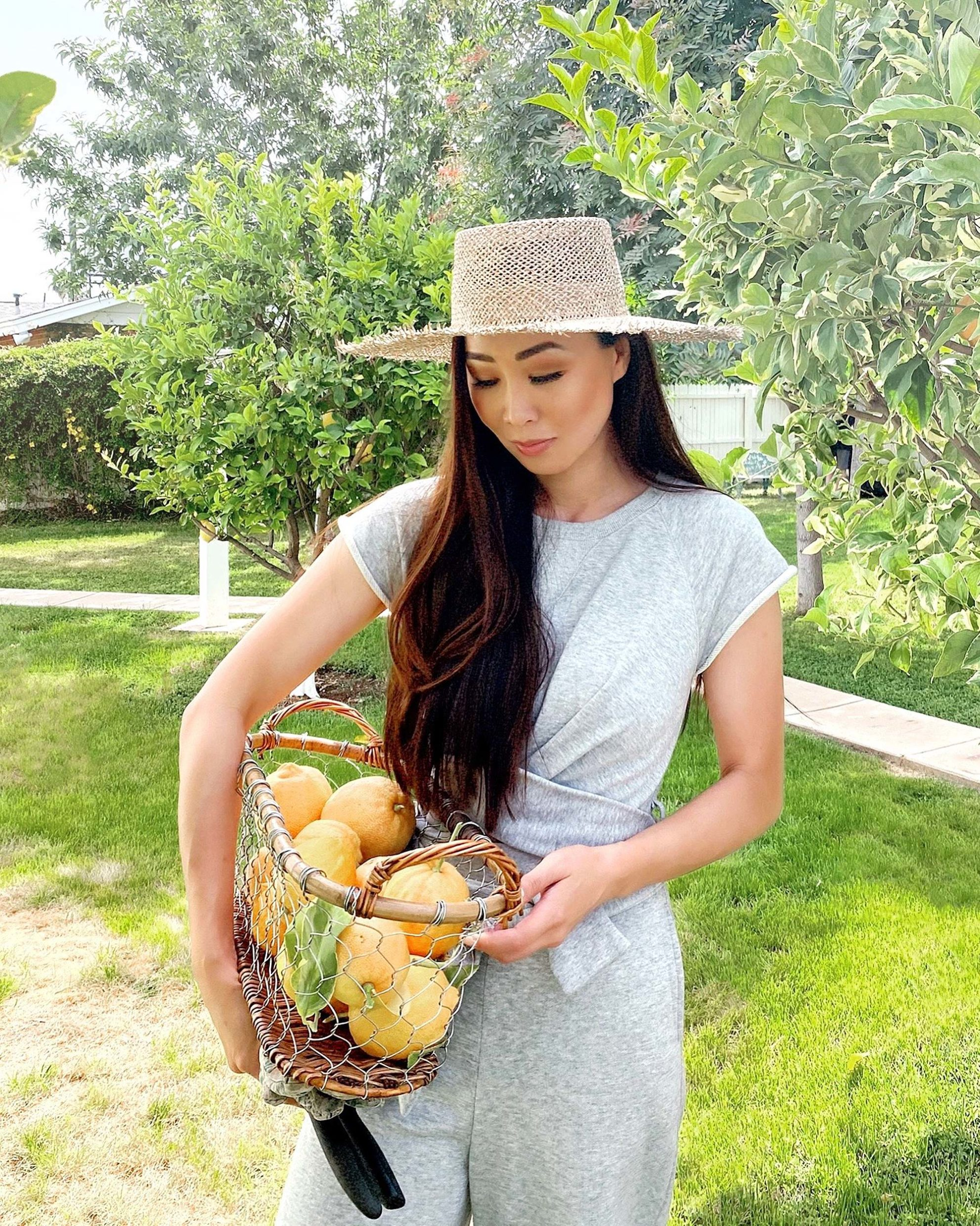 pink lemons in a basket, sweat jumpsuit straw hat garden lifestyle blogger Diana elizabeth