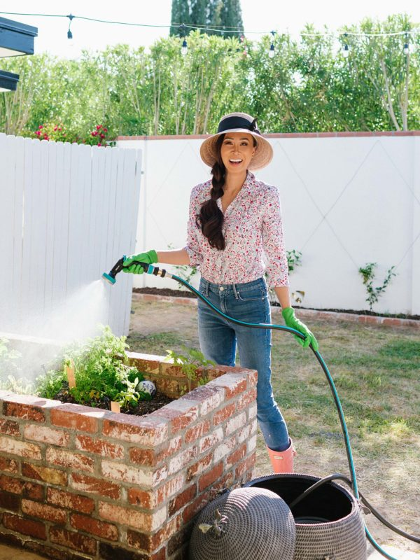 gardener holding hose by brick raised garden beds /lightweight durable hose by gilmour - garden backyard raised garden beds // arizona phoenix home and garden lifestyle blogger Diana elizabeth