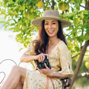odd Molly adore dress yellow dress / lifestyle blogger Diana Elizabeth holding fujifilm x100f camera sitting with straw hat on and yellow dress by a lemon tree #oddmolly #yellowdress