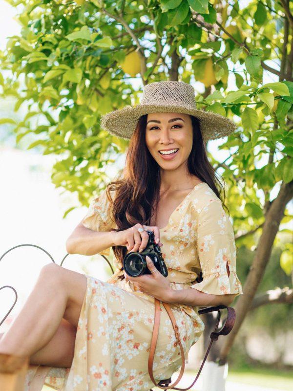 odd Molly adore dress yellow dress / lifestyle blogger Diana Elizabeth holding fujifilm x100f camera sitting with straw hat on and yellow dress by a lemon tree #oddmolly #yellowdress