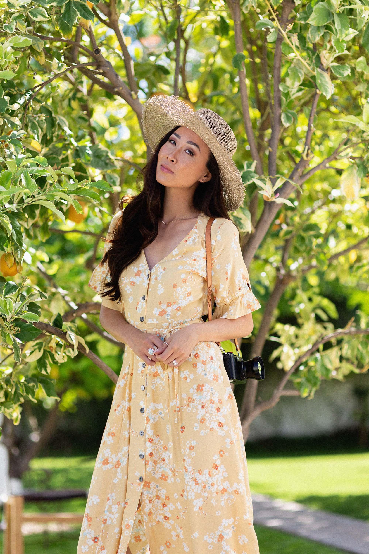 odd Molly adore dress yellow dress / lifestyle blogger Diana Elizabeth holding fujifilm x100f camera sitting with straw hat on and yellow dress by a lemon tree #springdress #yellowdress
