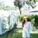running through home backyard orchard peach tree barefoot in lightweight dress and straw hat