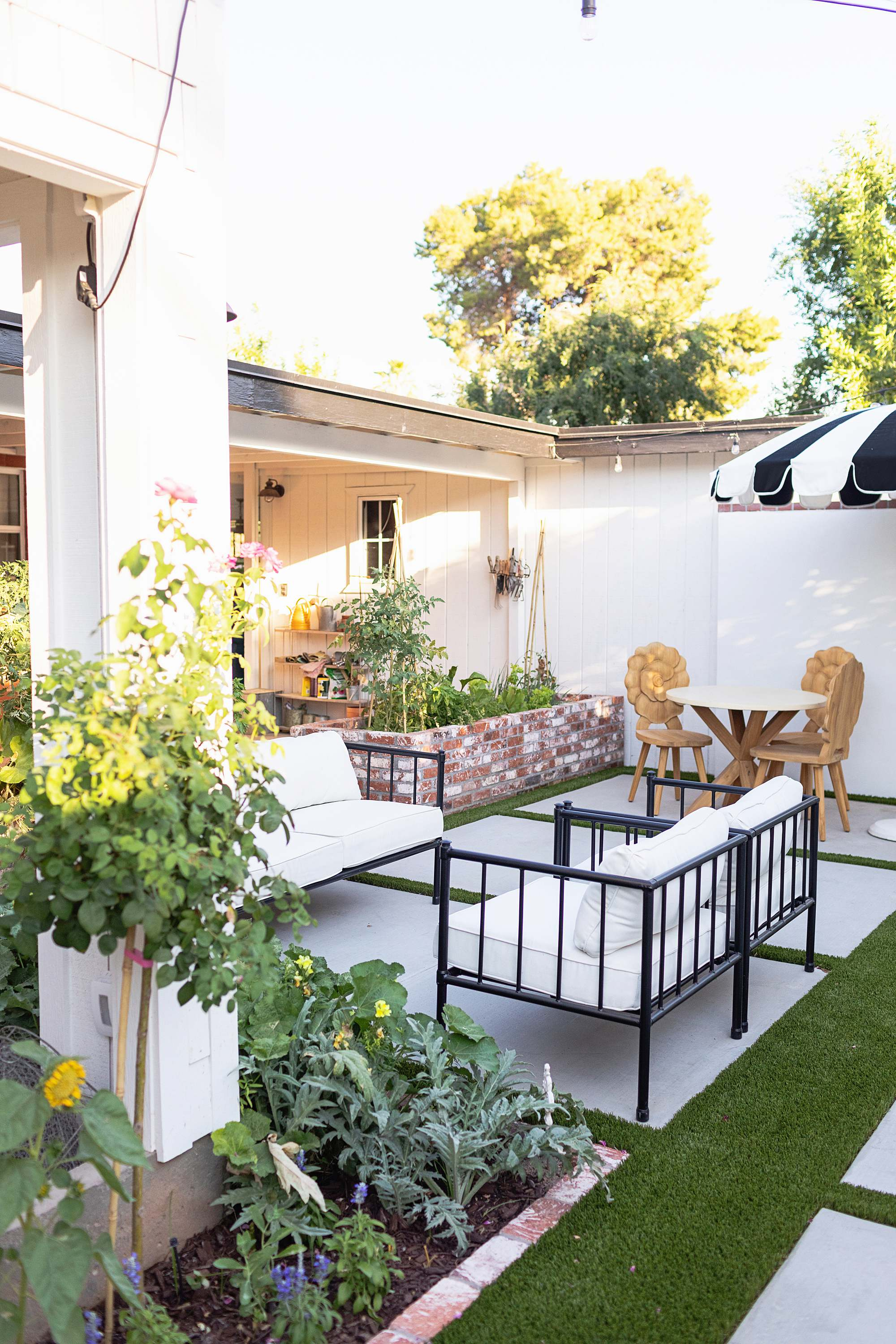 AFTER photos of new patio kitchen garden area - patio seating black and white with flower teak chairs #garden #backyard