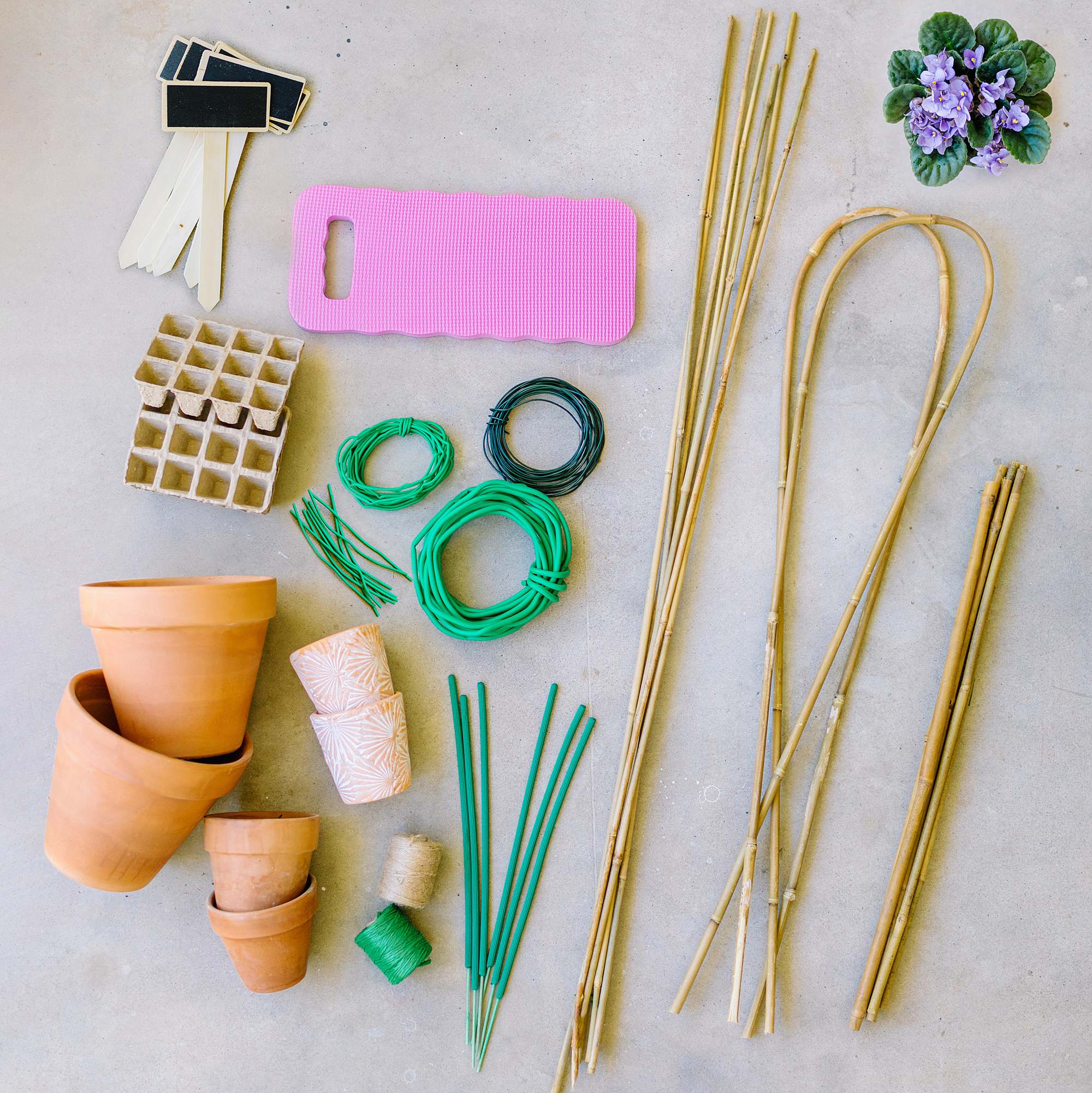 8 must-have gardening tools found at the 99 cents store - flat lay images of cheap gardening tools for under $1 - knee pad, paper pot, bamboo stakes, terra cotta pots, plant markers, rubber coated wire, citronella sticks, twine, and save money so you can buy more plants! #gardeningtips