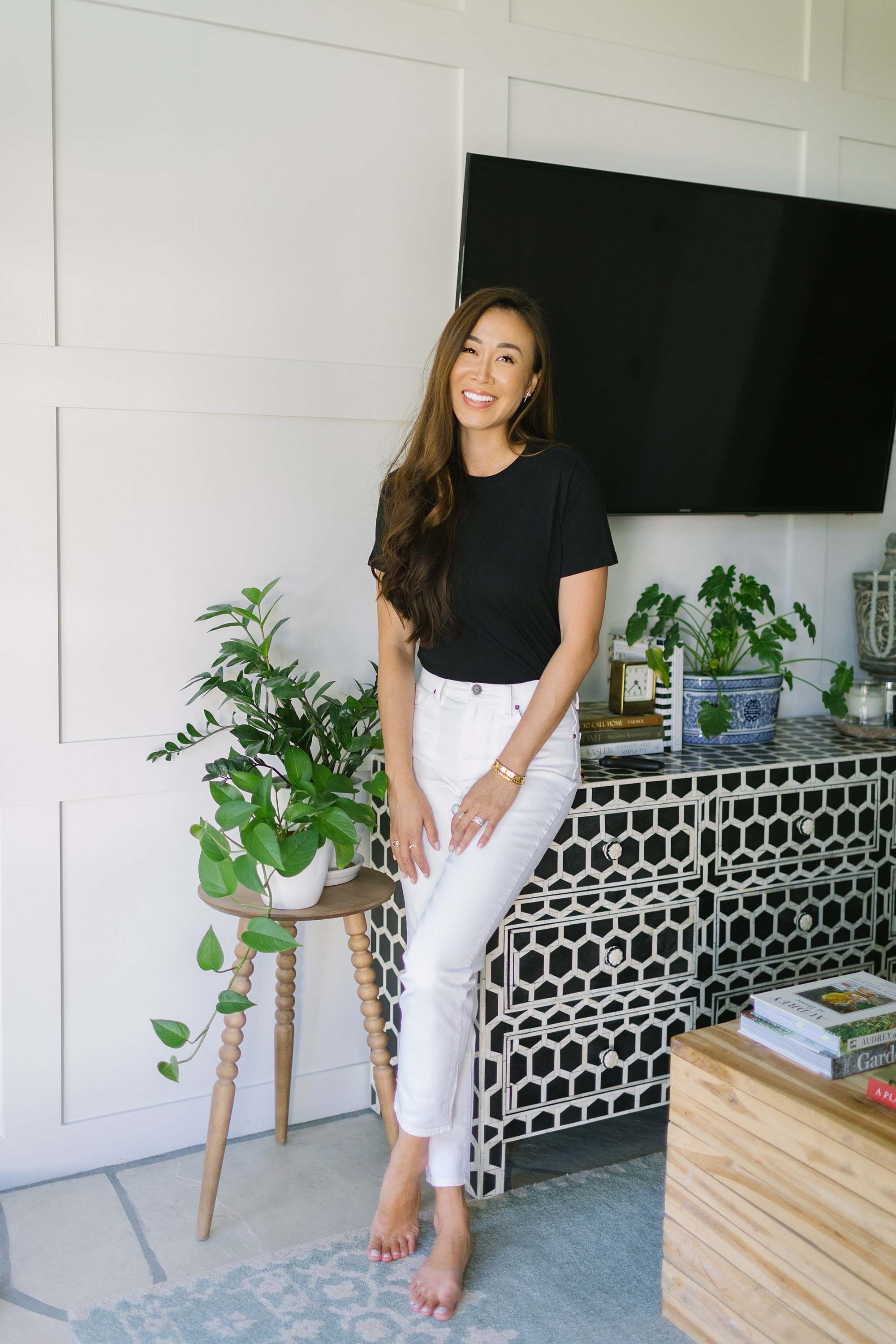 Diana Elizabeth phoenix lifestyle blogger in white pants blacks shirt leaning against black and white bone dresser by lots of house plants. jeans and top by Mott and bow