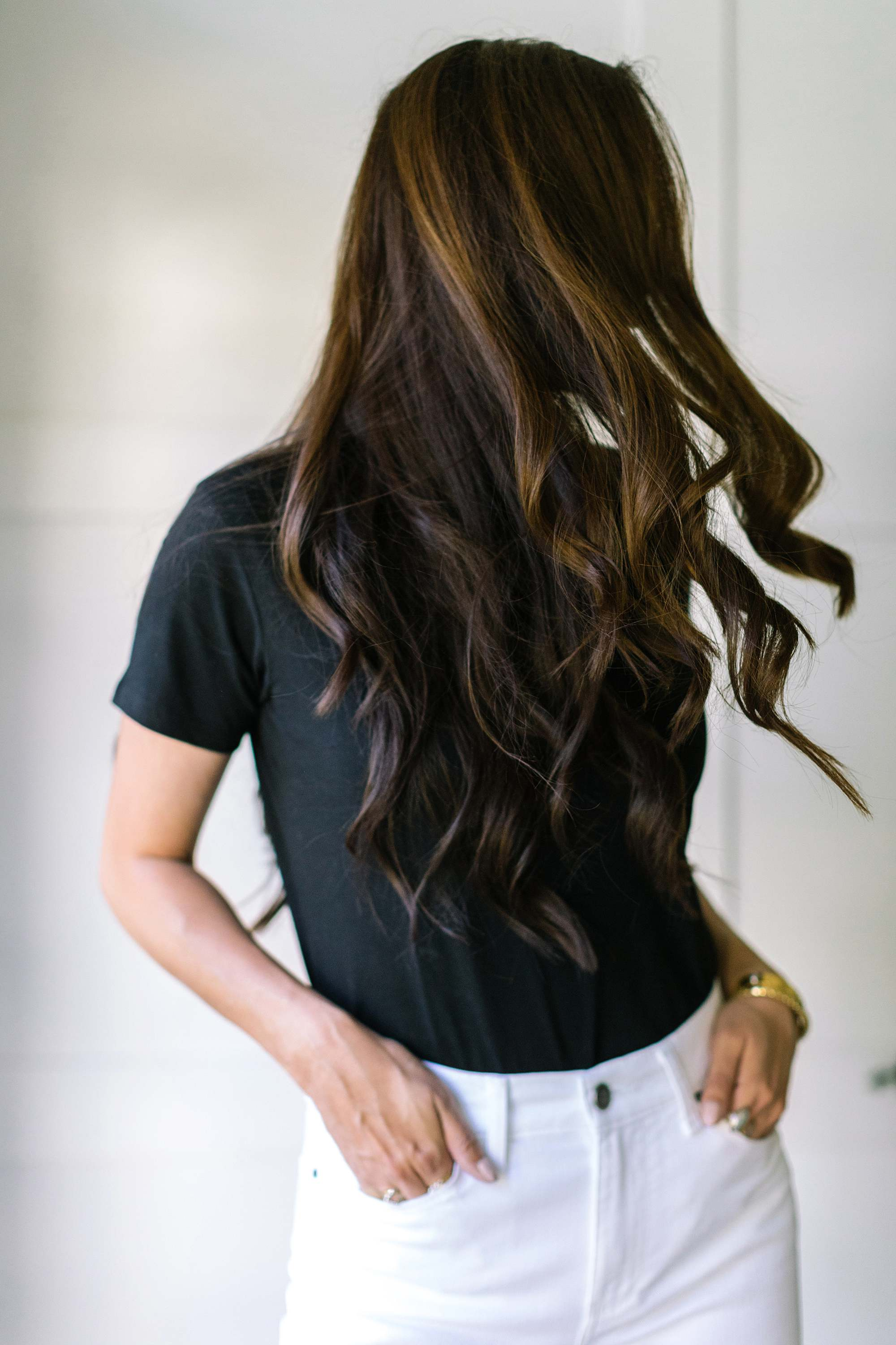 hair swing wearing black top and white jeans