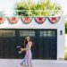 Fourth of July theme garage with American flag bunting on white garage with black garage door