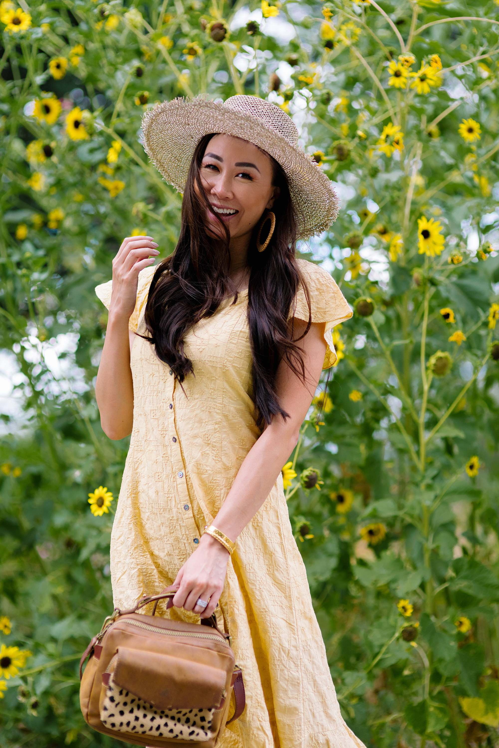 odd Molly Capri dress in yellow standing in front of sunflowers