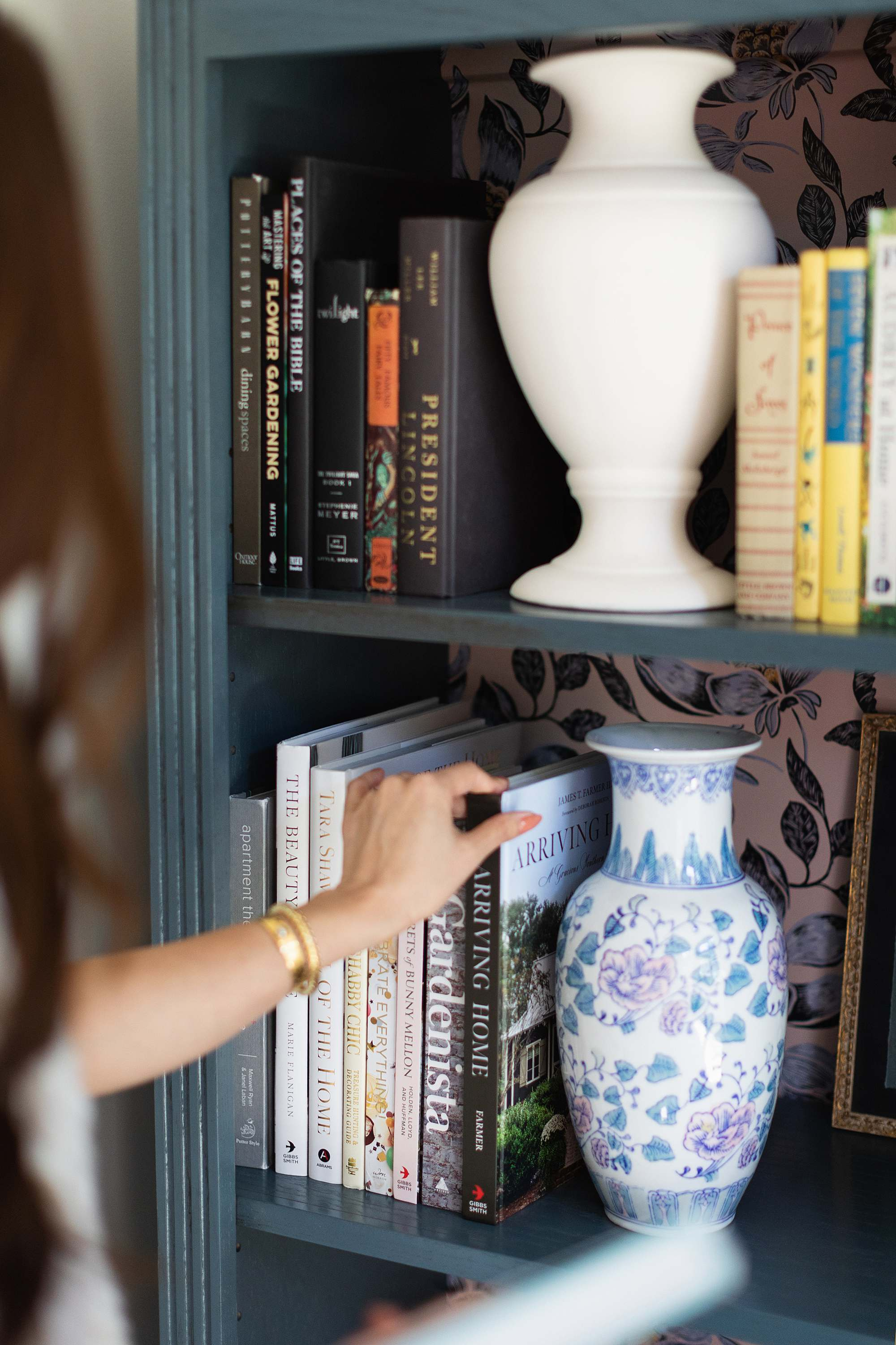 7 favorite interior design books coffee table books // woman holding books by bookcase