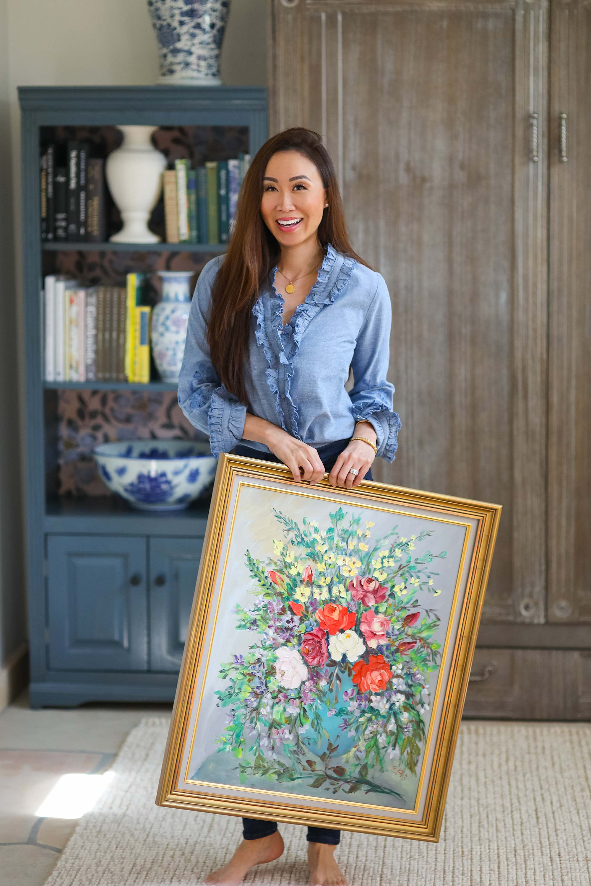antiquing, thrifting, and buying new like at home goods, what do I like to buy and where // holding antique floral oil on canvas painting - home and lifestyle blogger